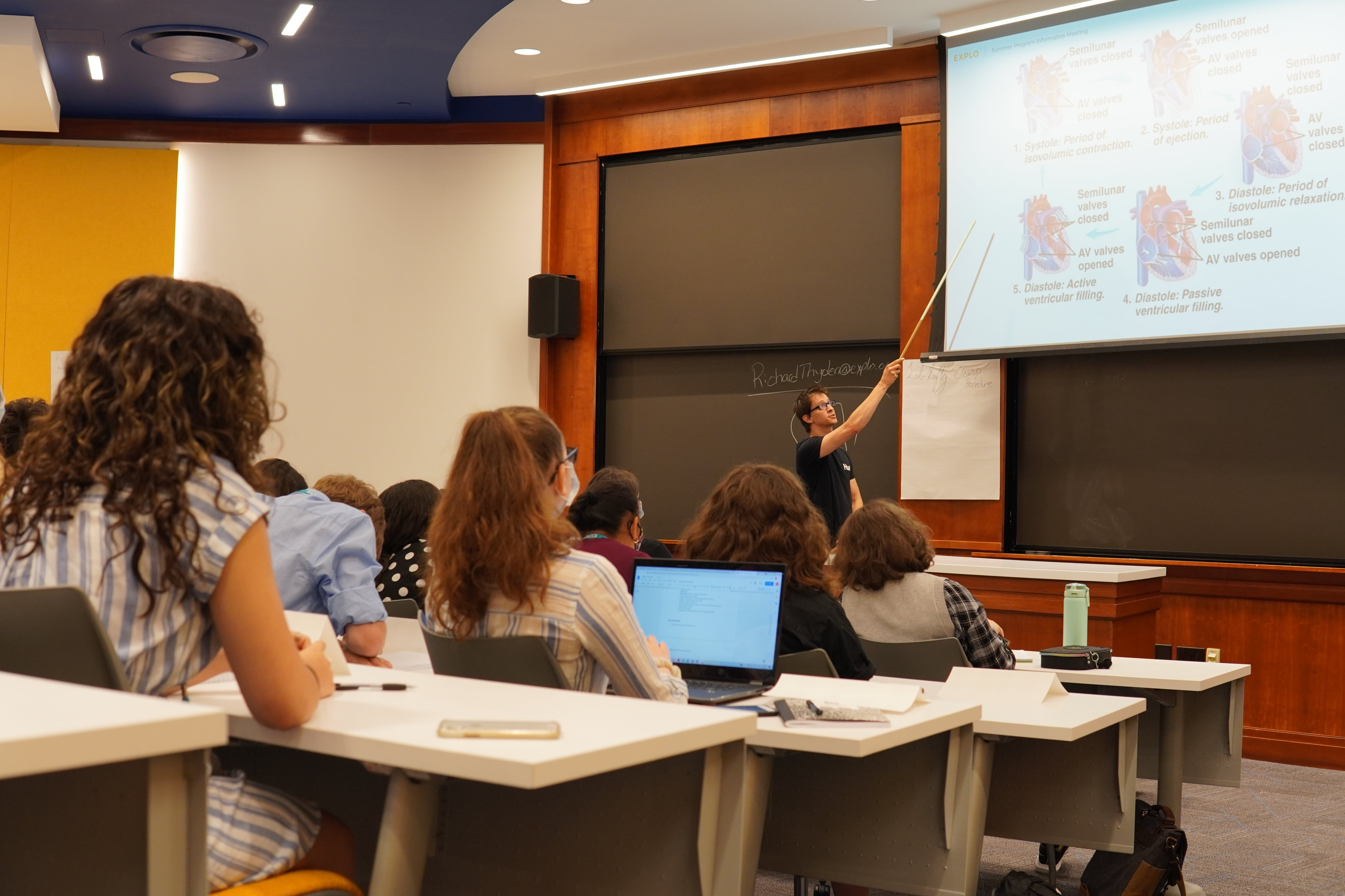 Students in four rising rows of desks watch as their instructor points to a diagram of the heart projected above him