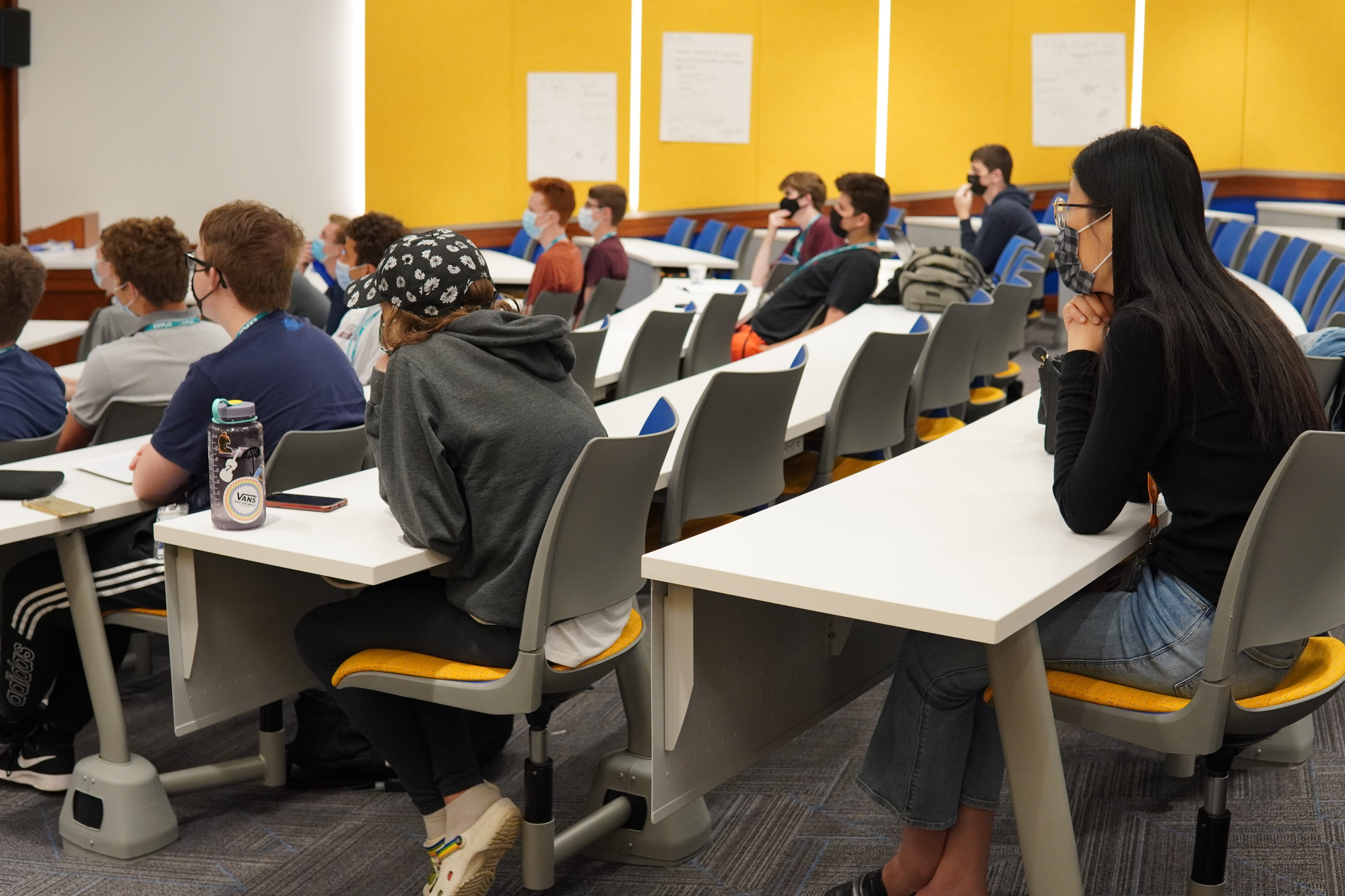Lead Instructor Ann sits in the back of a lecture hall as the students in front of her listen to their guest speaker, Professor Terry Yoo.