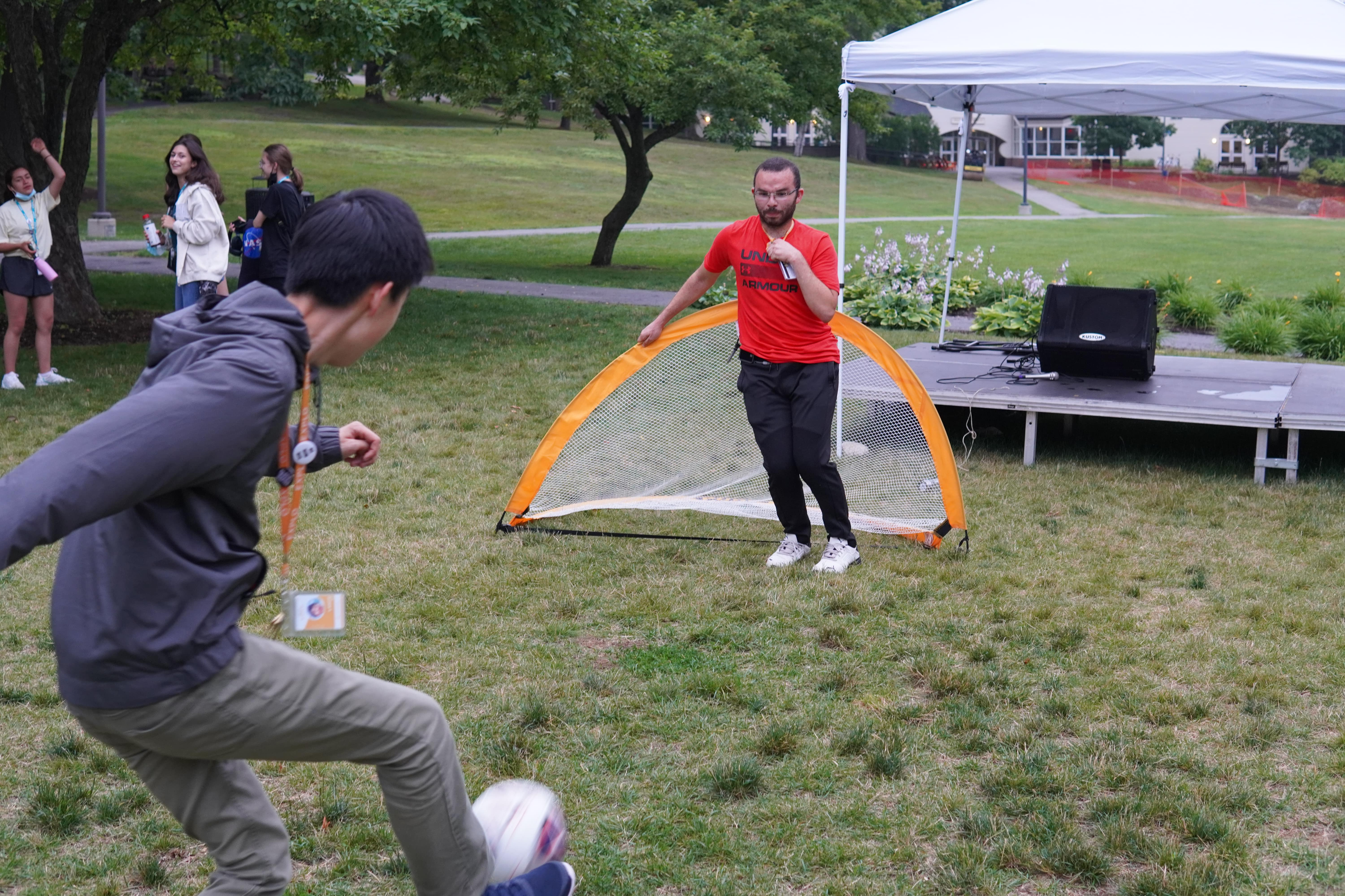 A staff member kicks a soccer ball toward another standing in front of a goal in a soccer game on the quad.