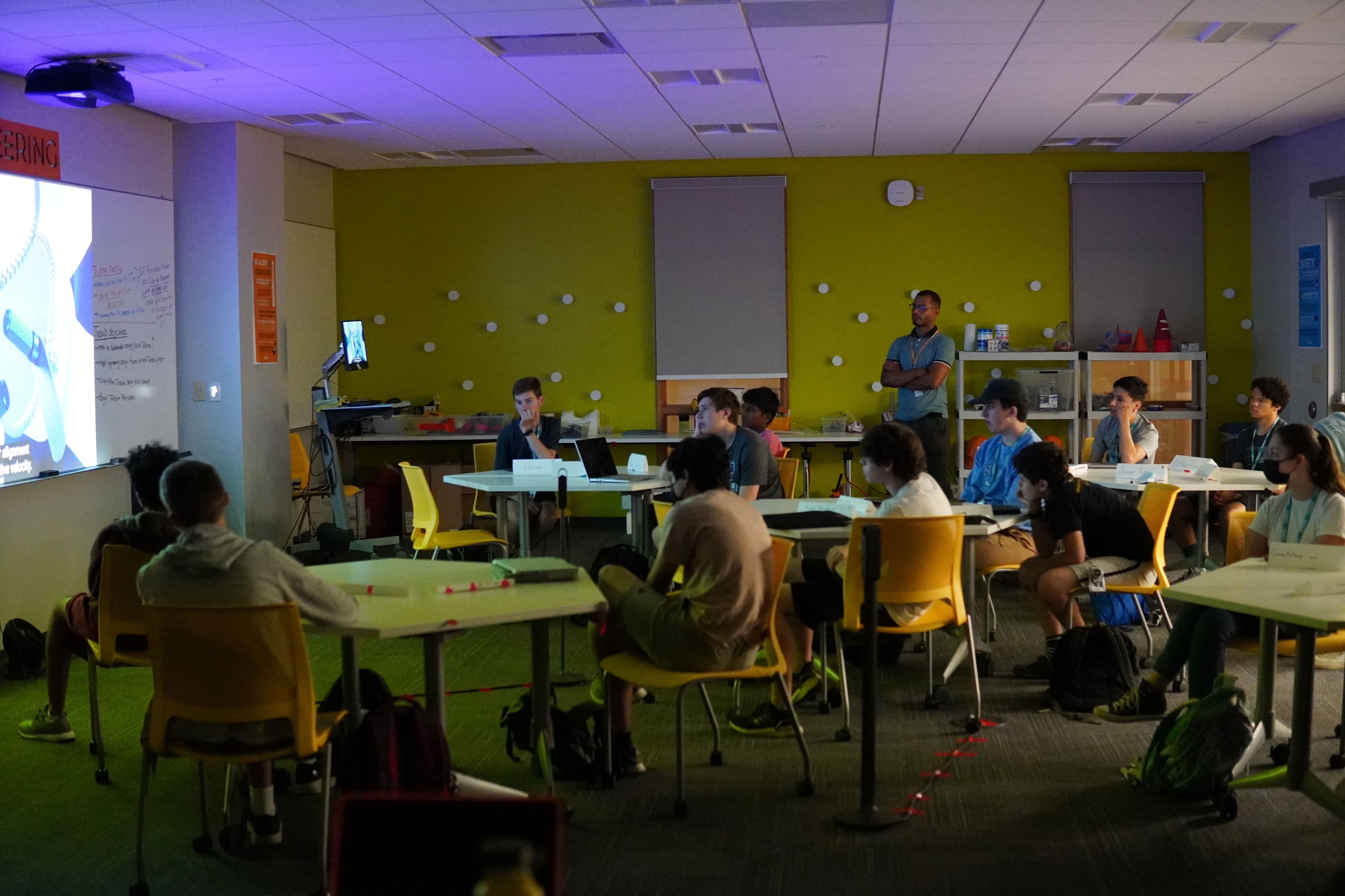 Students sit in a room watching a video projected in front of them.