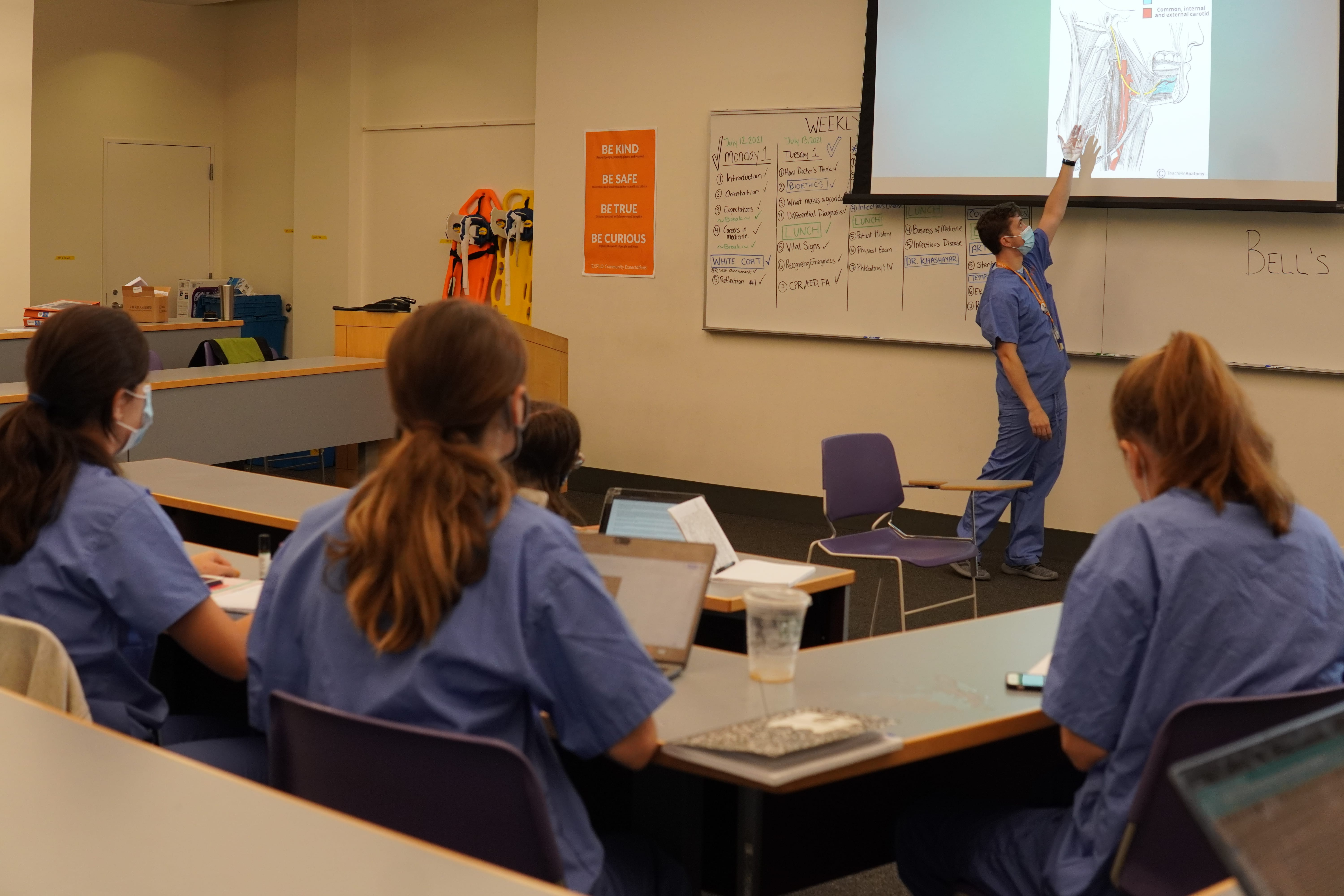 Students sit a lecture hall listening to their instructor as he gestures to a chart depicting the throat.