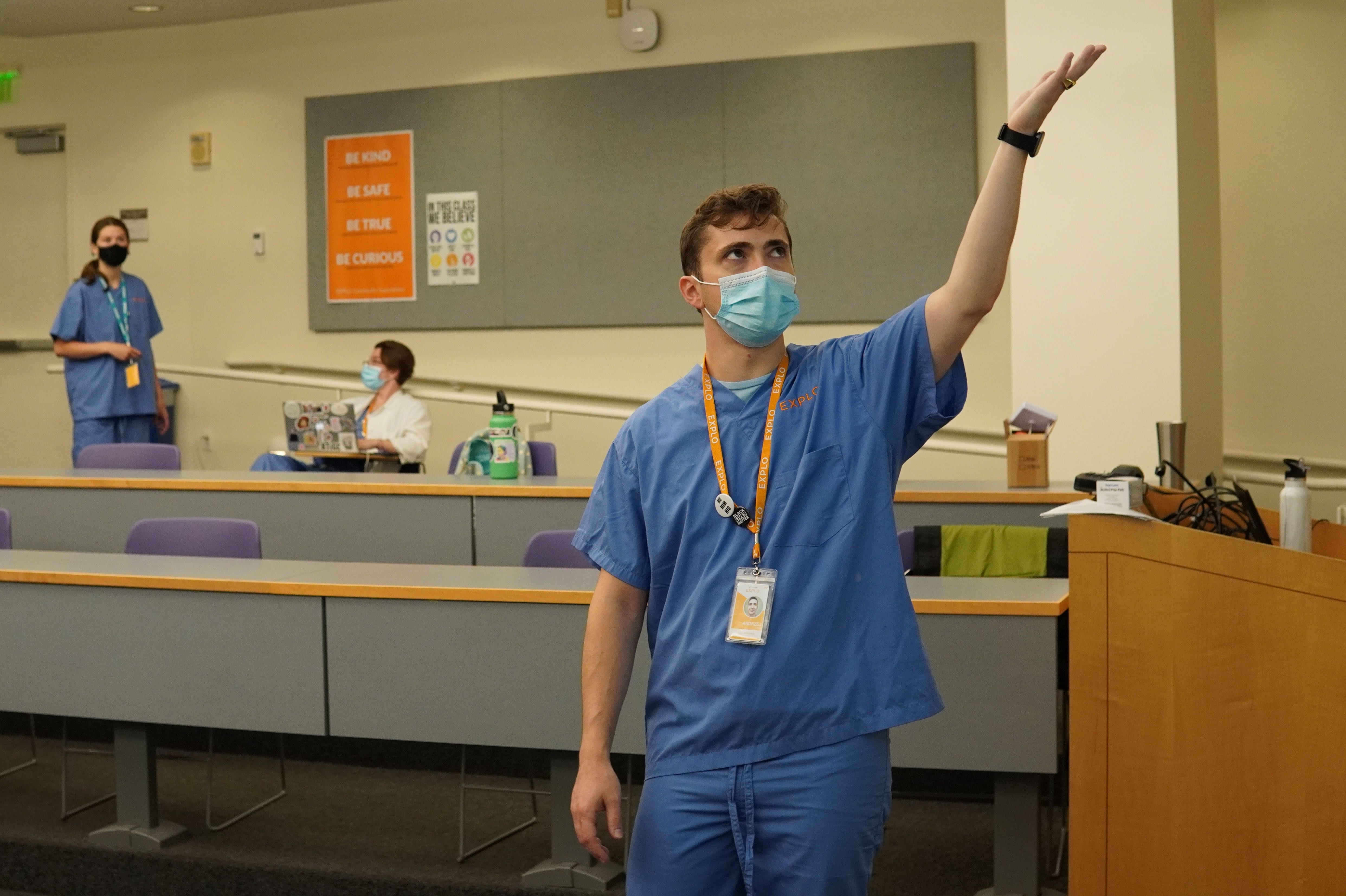 Leading Instructor Andrej gestures up toward the projection out of frame as he explains lab safety procedures.
