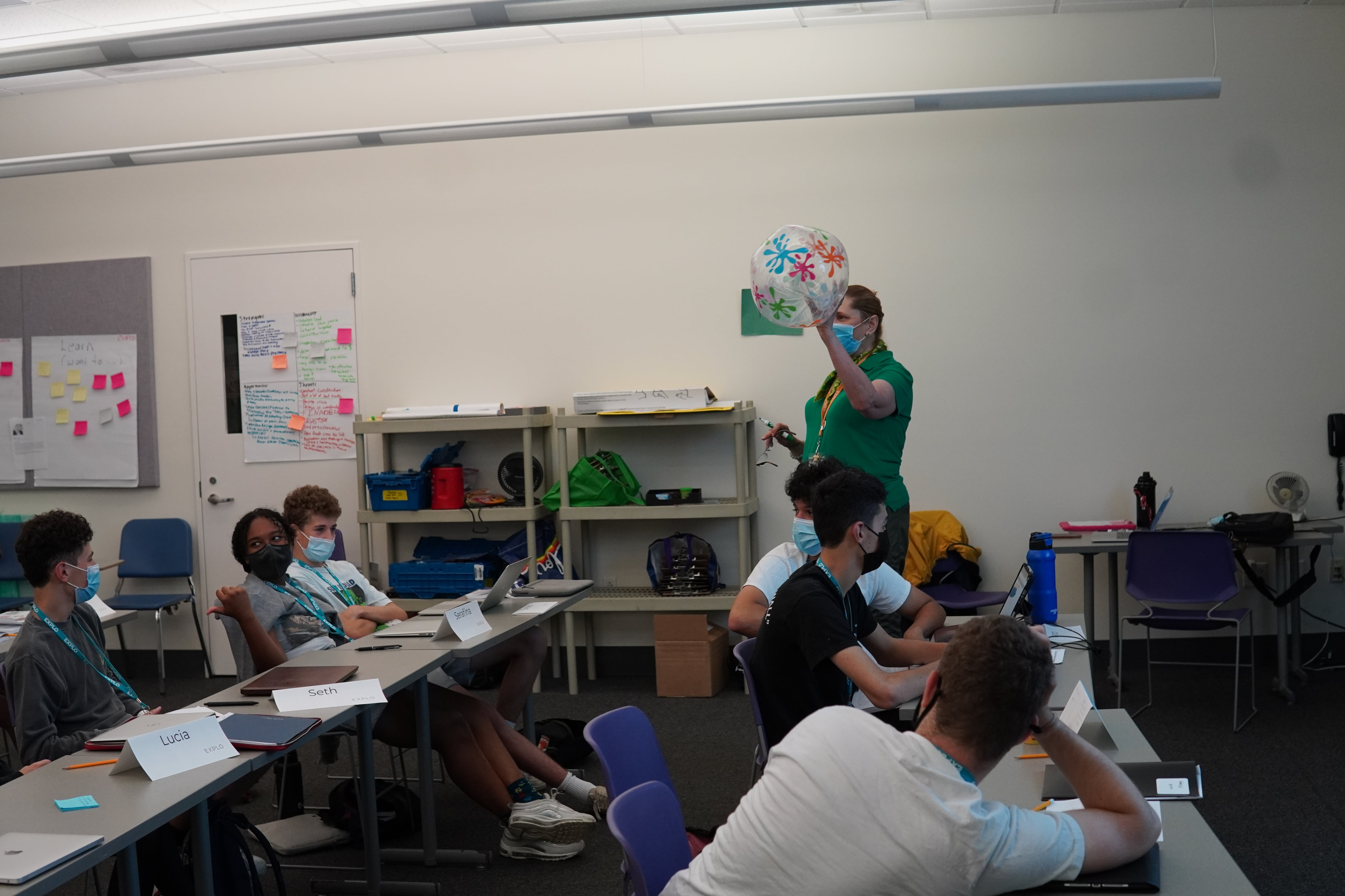 Lead Instructor Michelle holds up a beach ball to toss toward a student as a signifier as to who can answer a question.