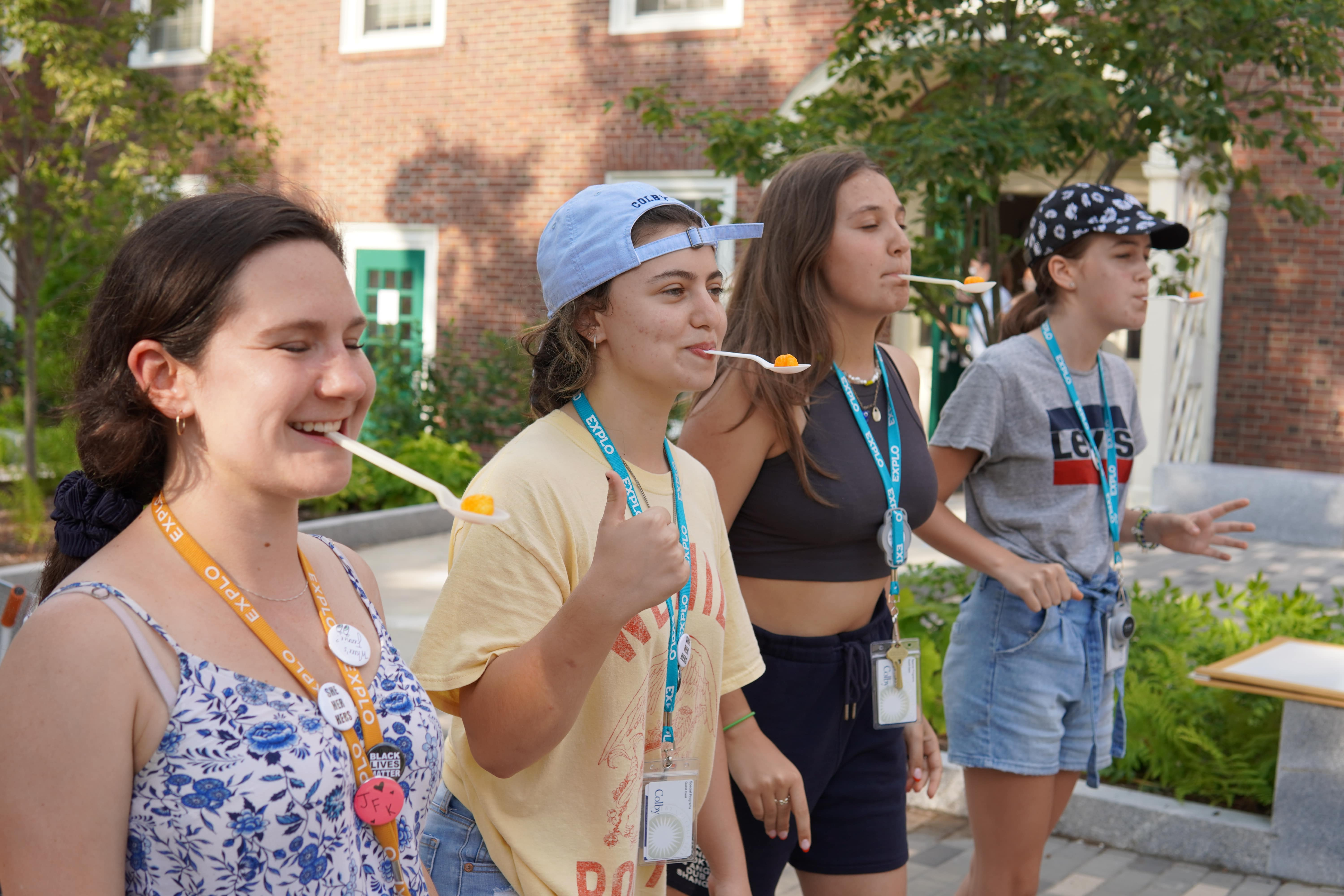 Students and a staff member line up with spoons holding a cheeseball in their mouths for the first race of the games.