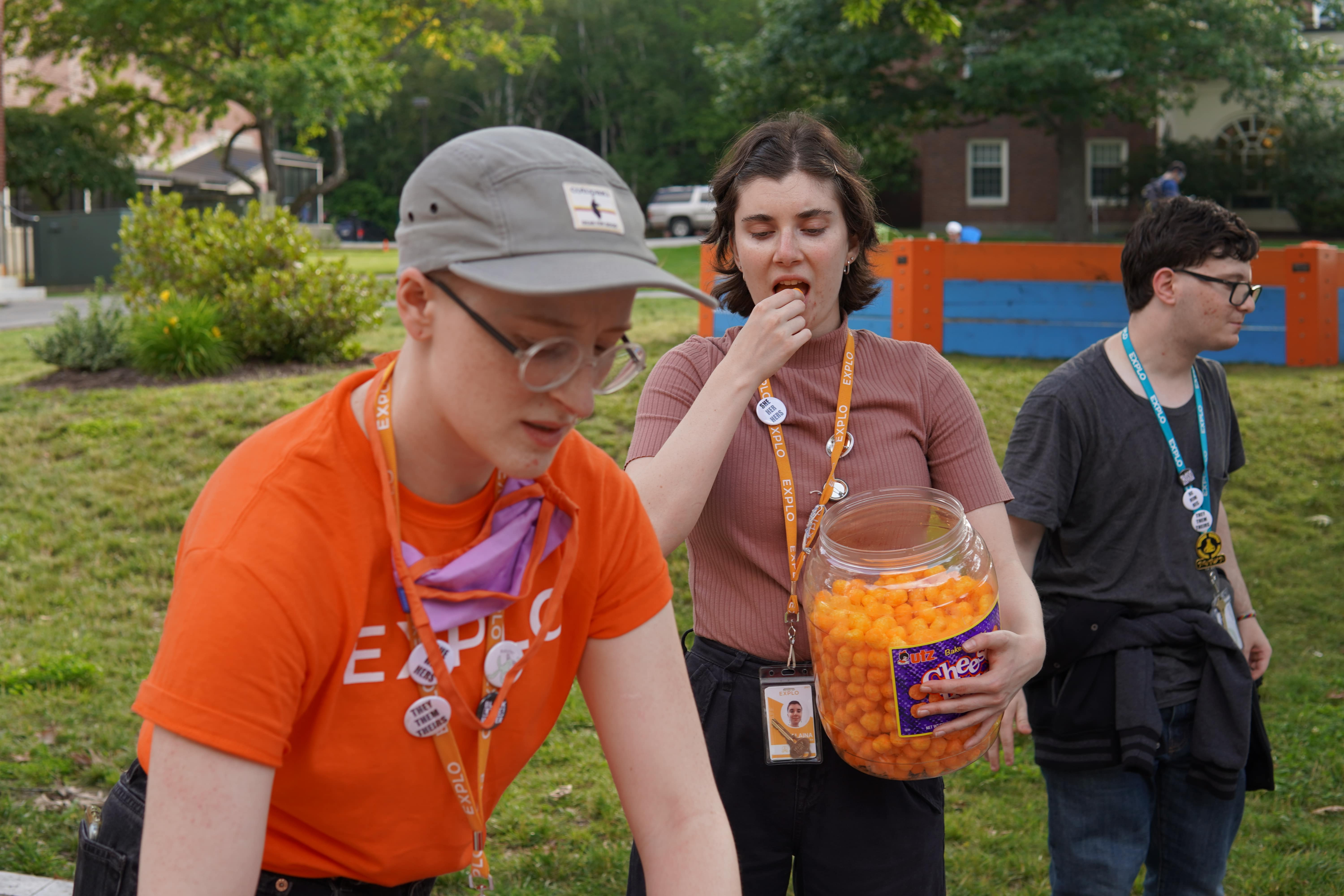 A staff member in an EXPLO shirt makes preparations for the cheeseball olympics as another one behind her snacks on cheeseballs.