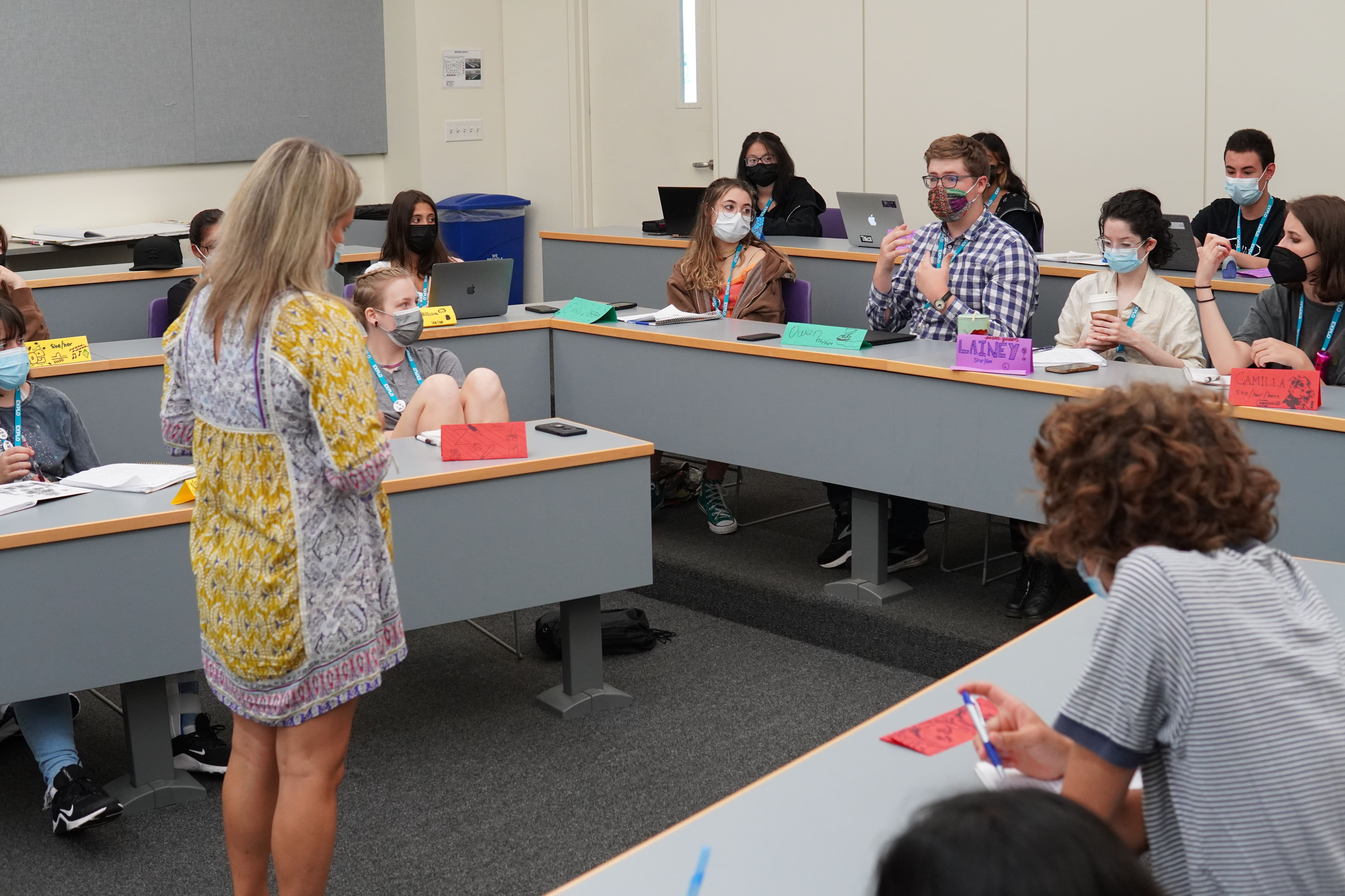 A student speaks from their seat in a lecture hall as students and Lead Instructor Lori turn to listen.