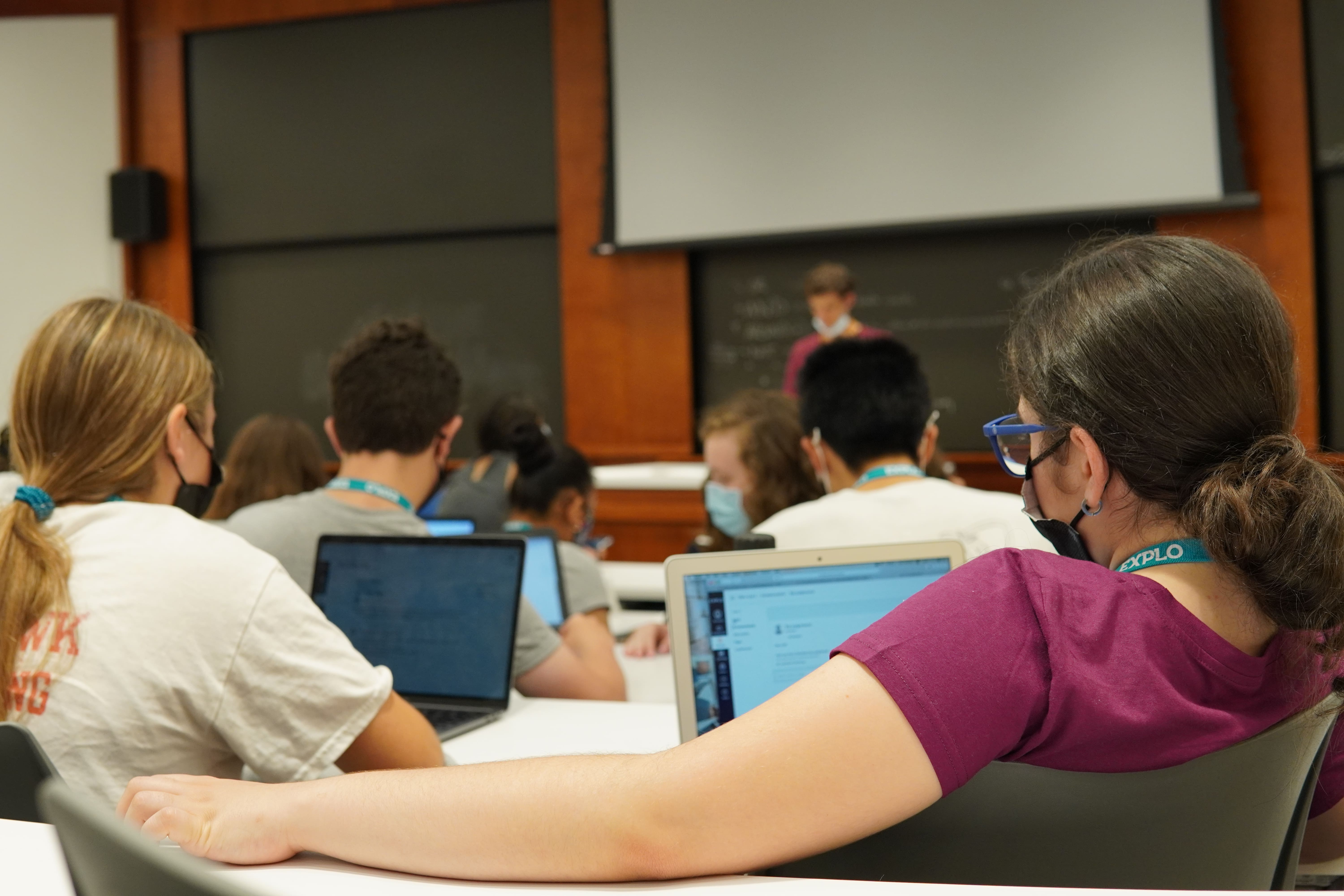 A student sits in the back of a lecture hall taking notes with the others, their arm laid out on a desk behind them.