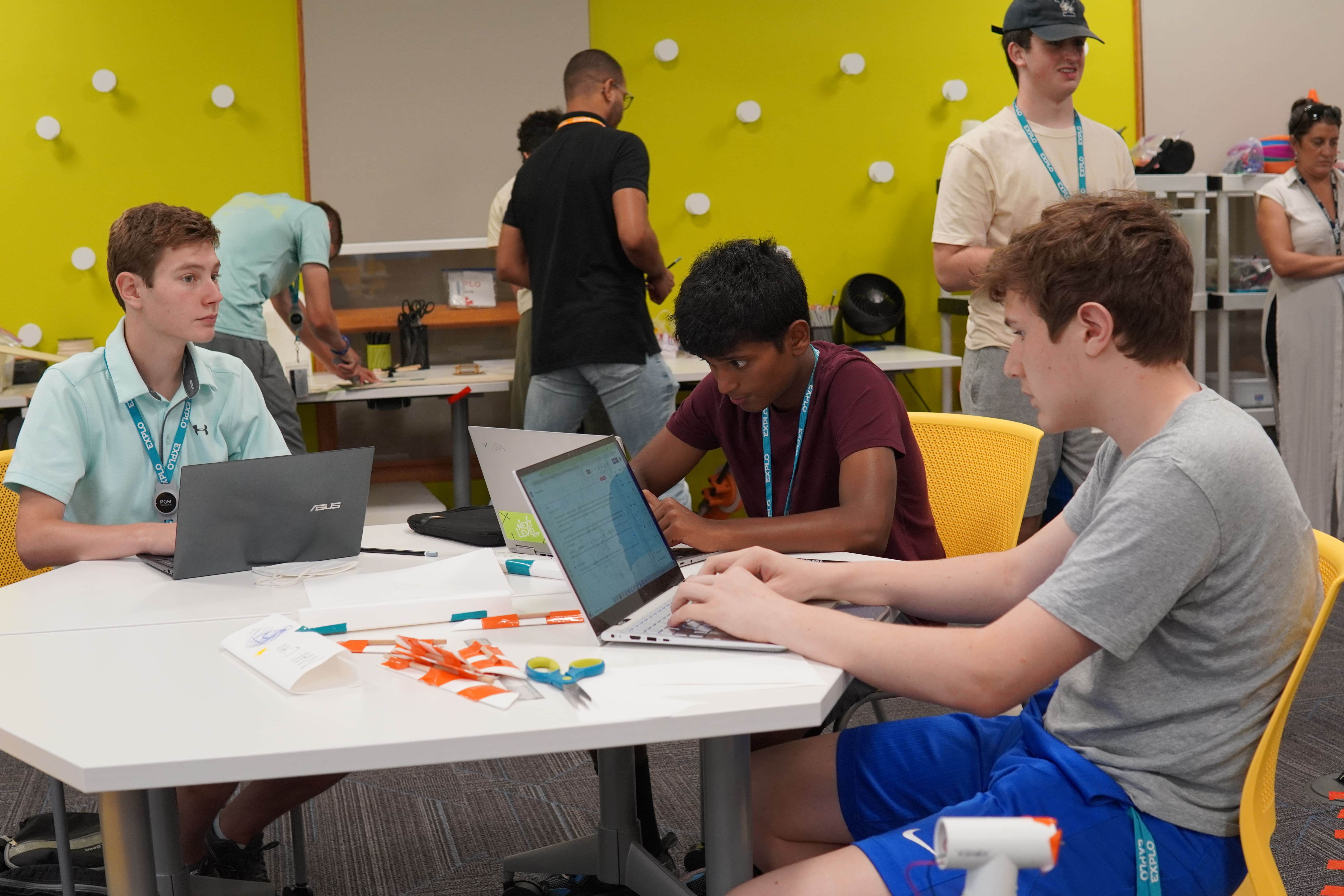 Engineering students work on their computers and at a work station in the background while designing and building their wind turbines.