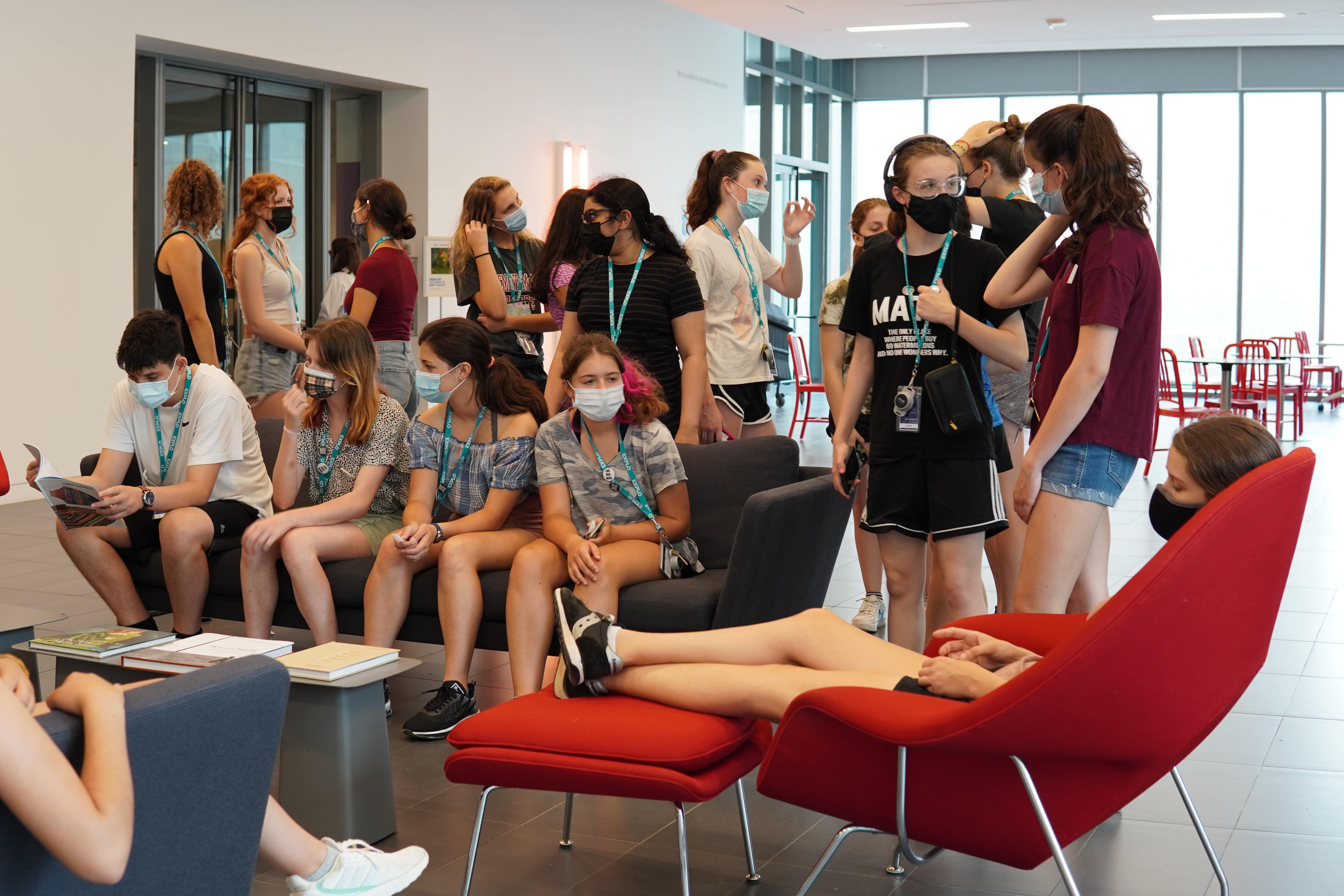 Students meet in the entrance to the Colby College Museum of Art and sit on the couches.