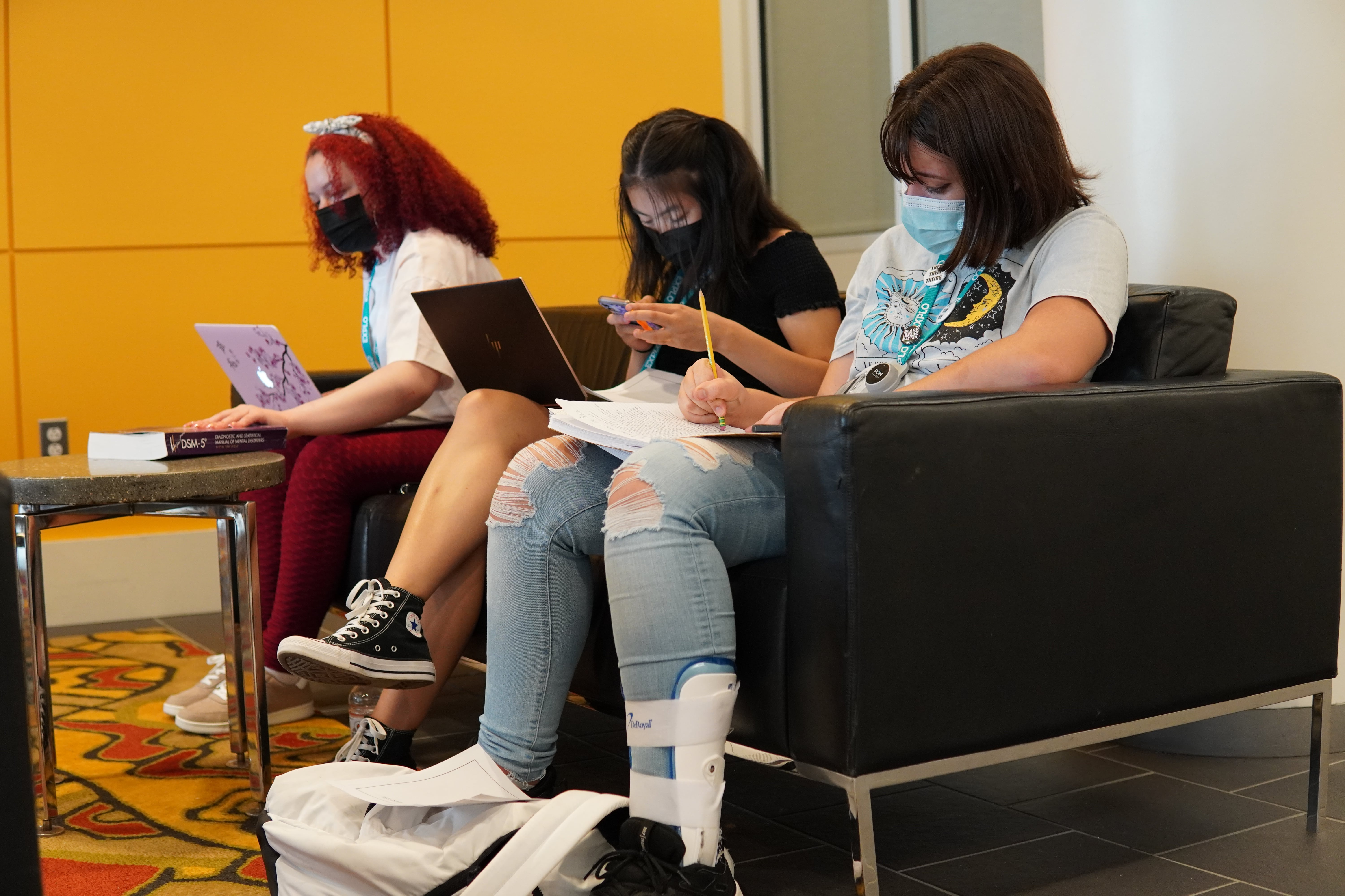 Three students sit on a couch together with their laptops open for research.