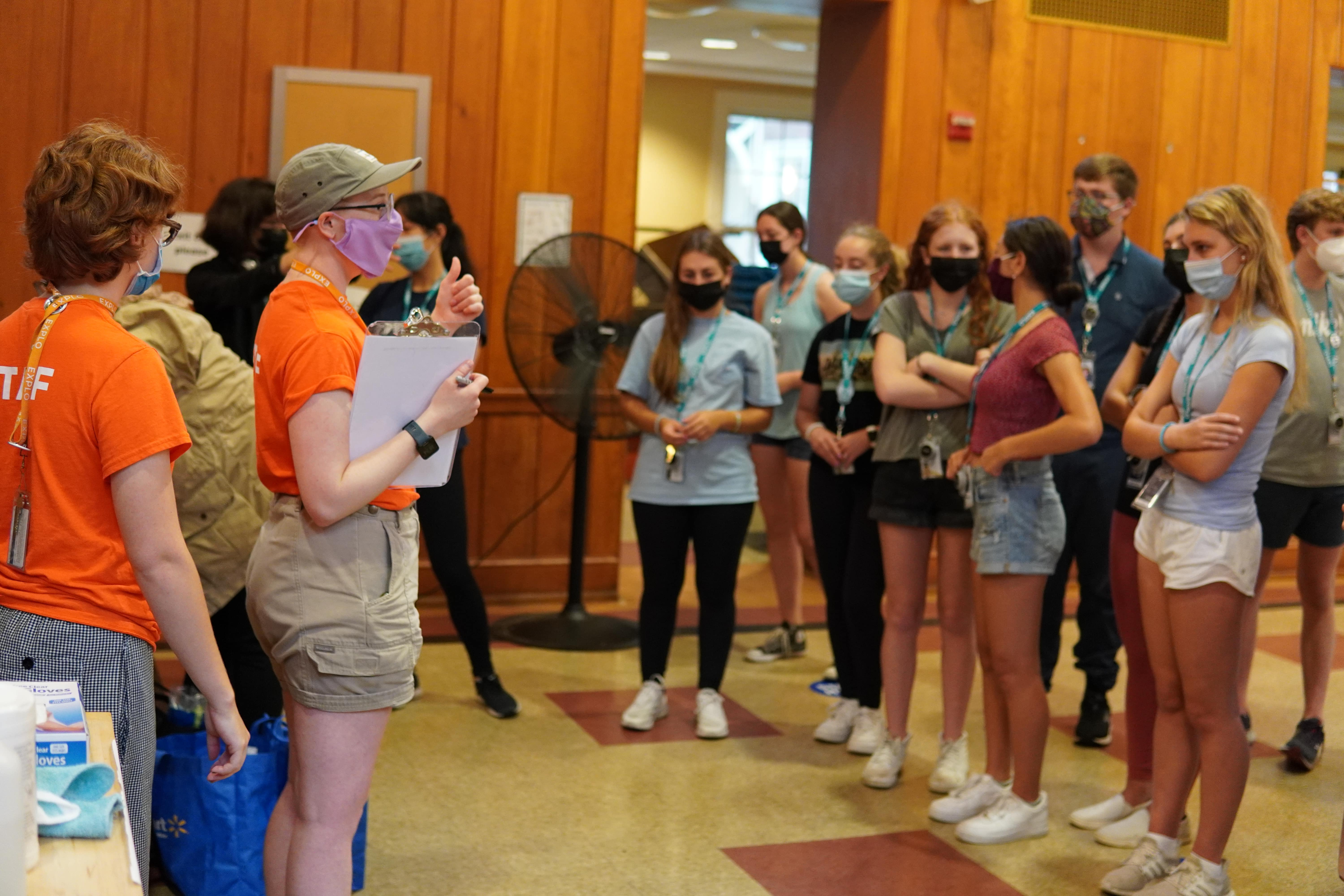 Staff members explain the competition's rules and reveal the secret ingredient to a small crowd of listening students.