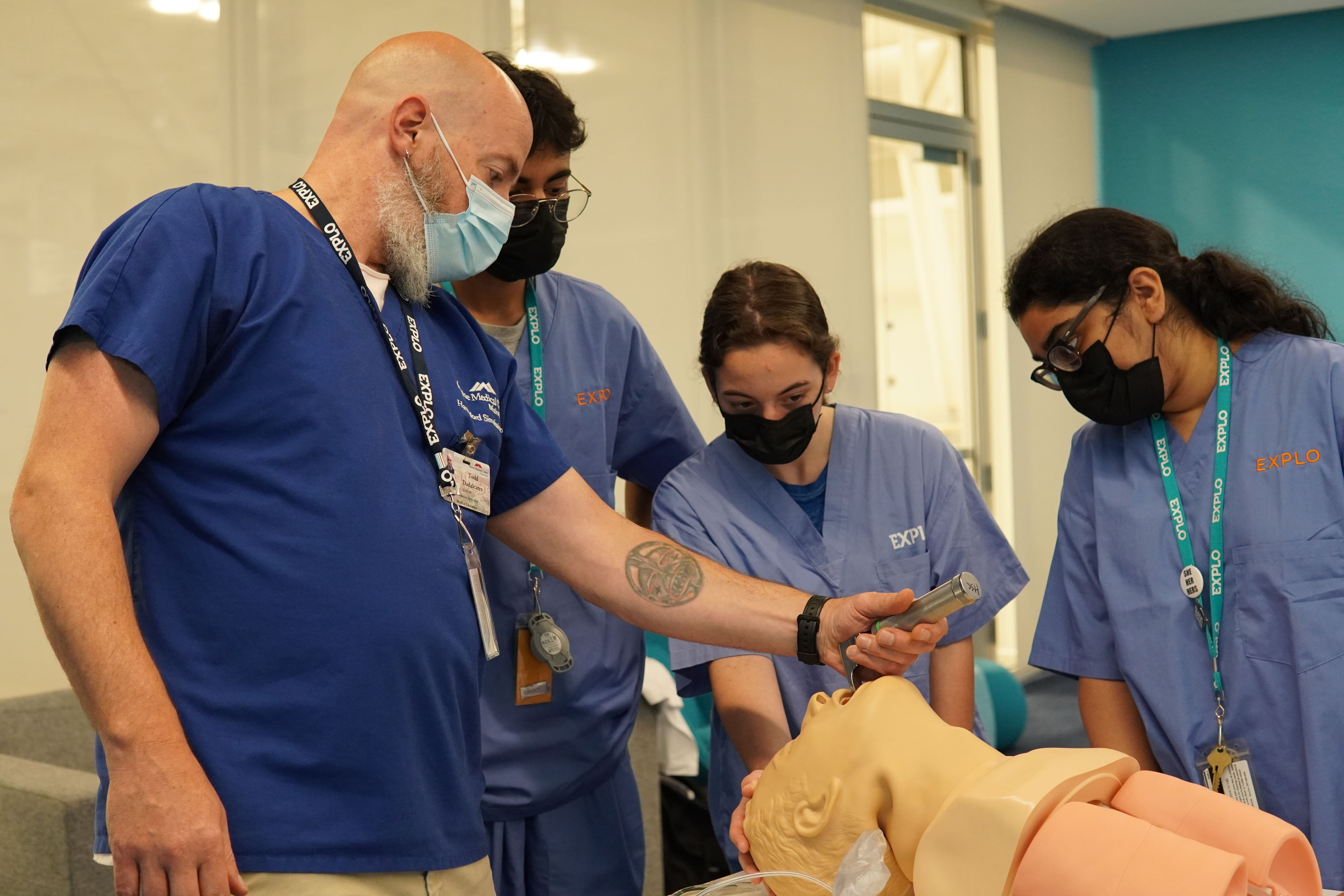 A guest instructor shows students how to intubate a patient on a dummy.