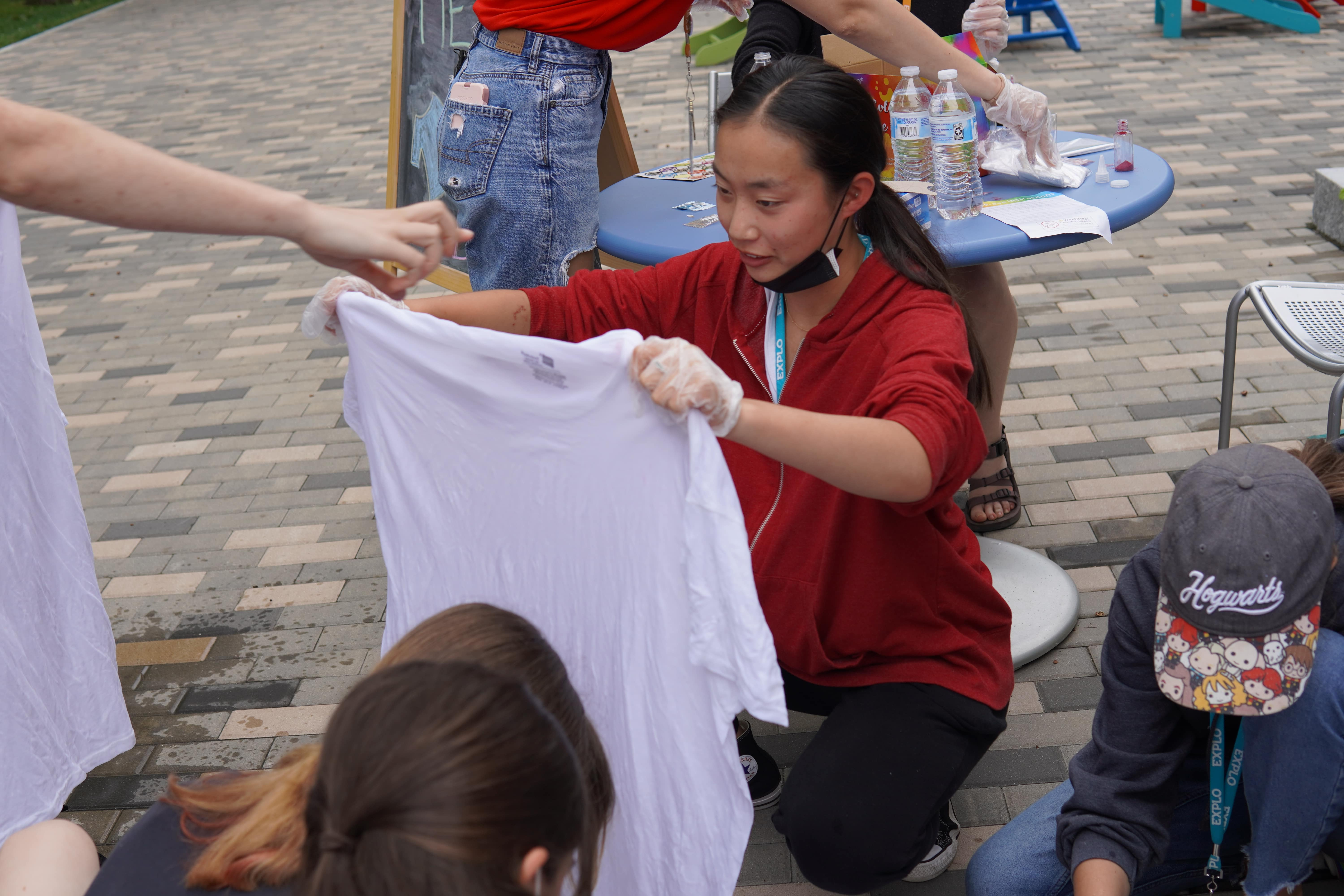 A student kneels with a white shirt before submerging it in water before the dyeing process.