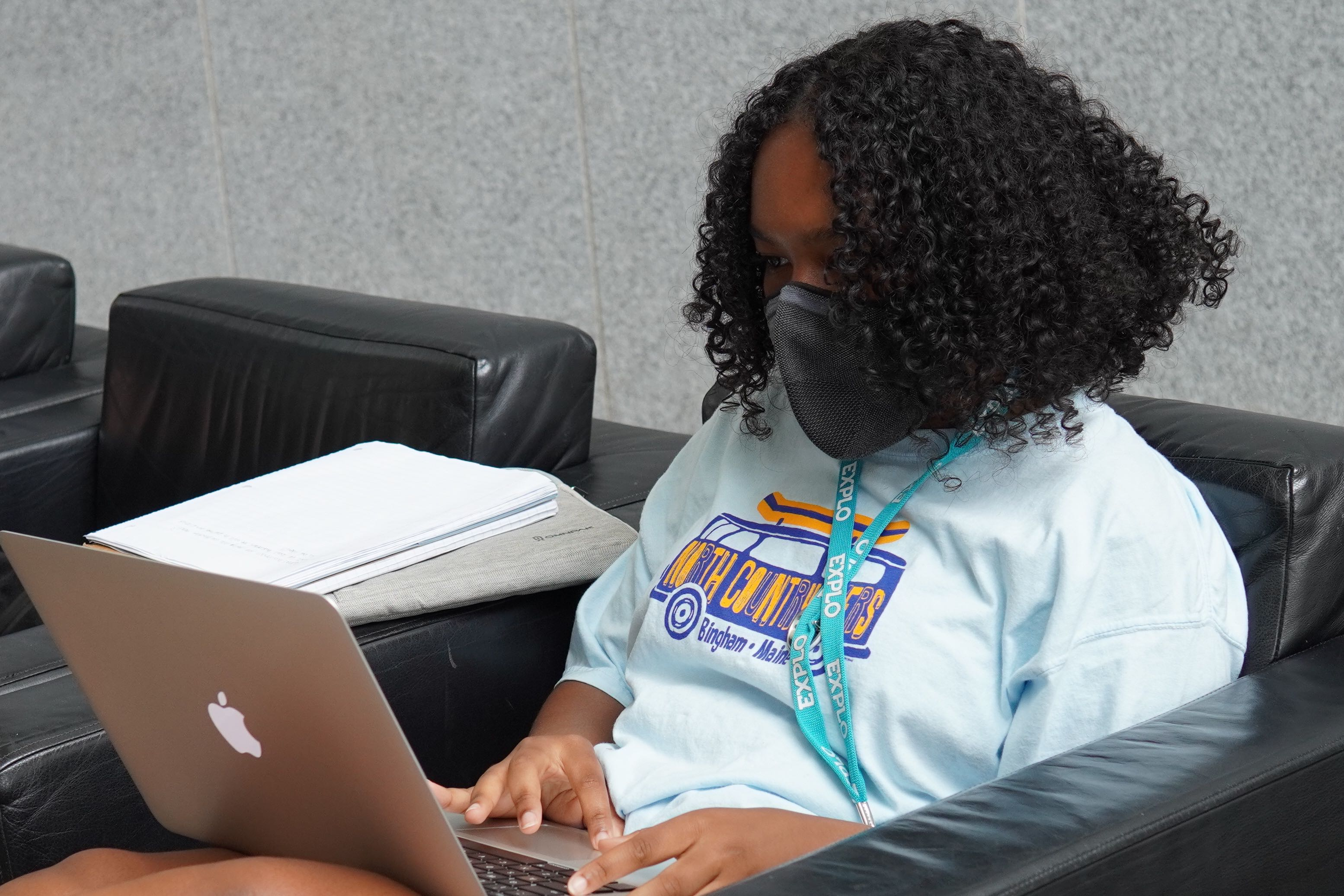 A student works on a laptop in a black chair.