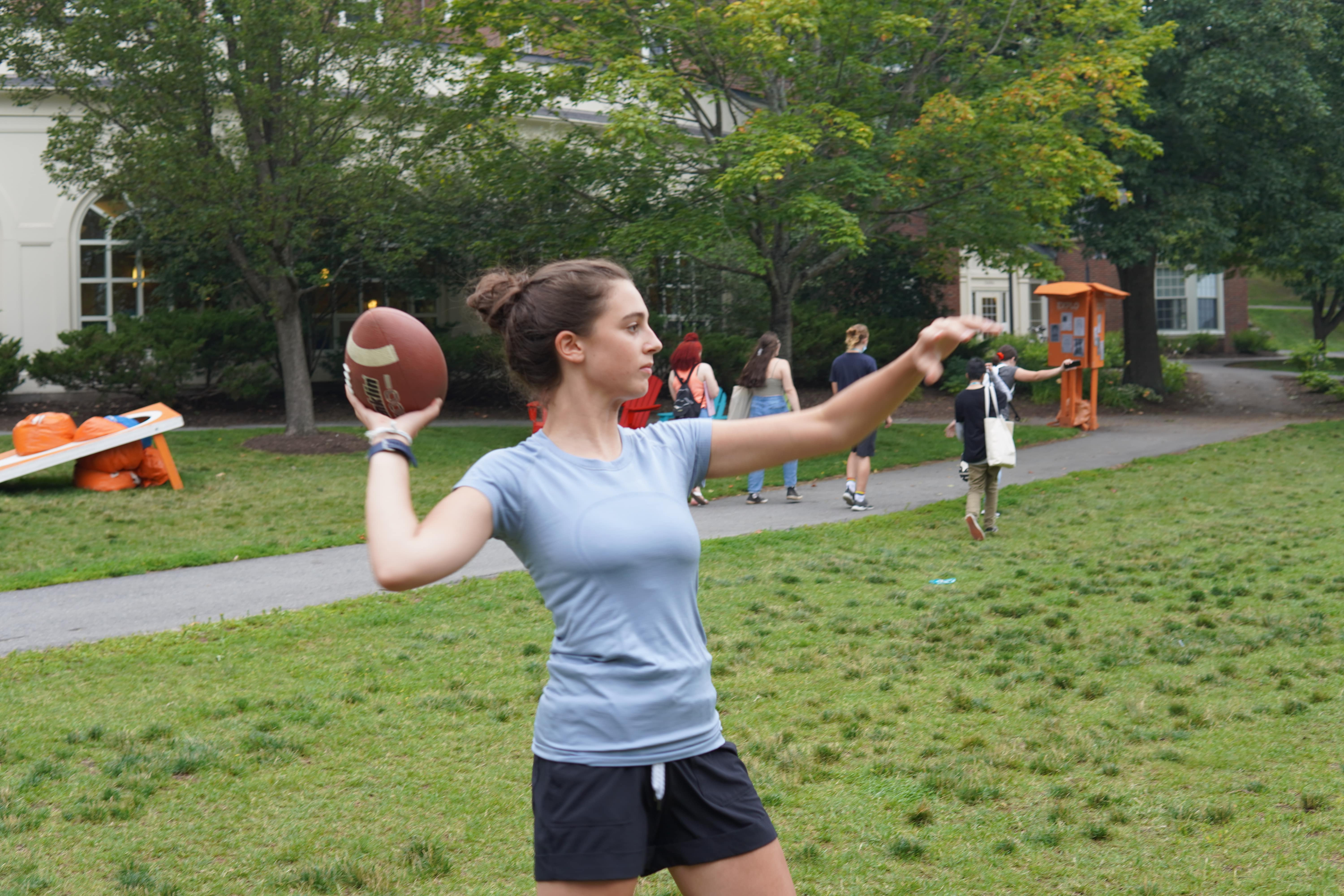 A student pulls their arm back before throwing a football.