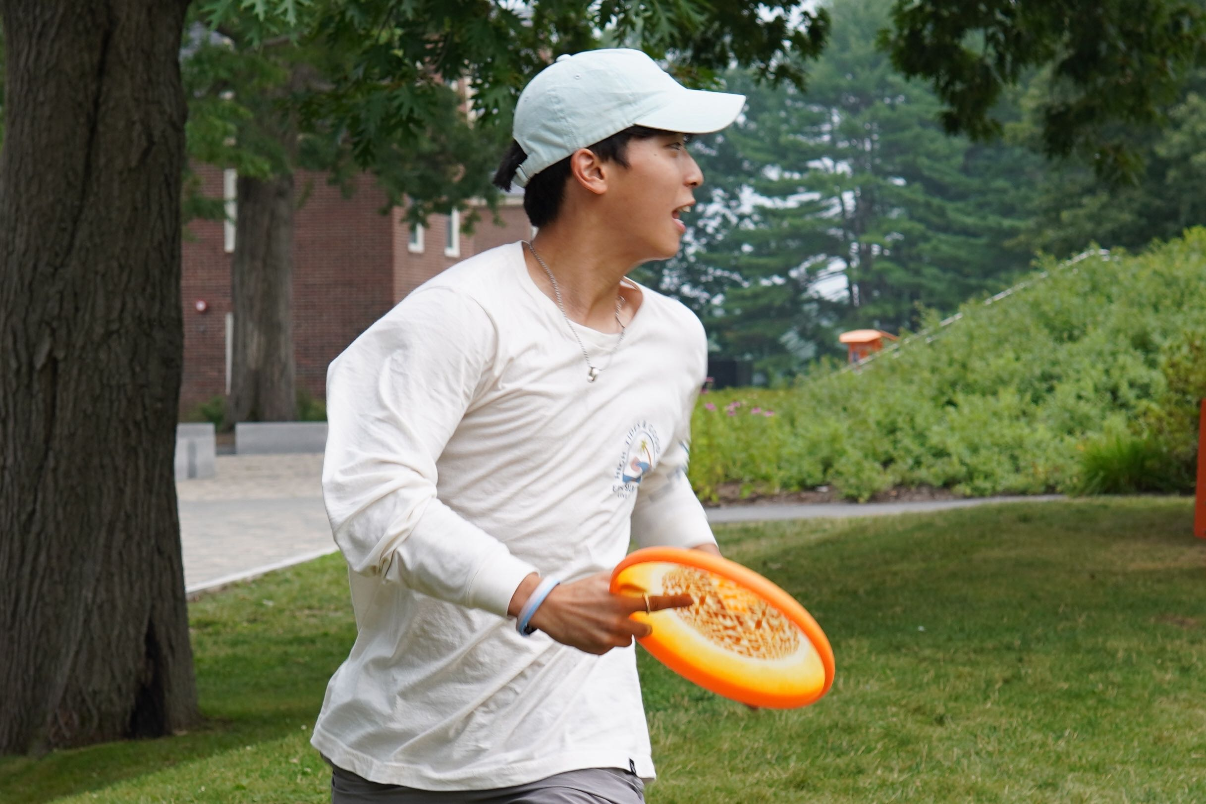 A student jogs to a stop on the quad after catching a frisbee