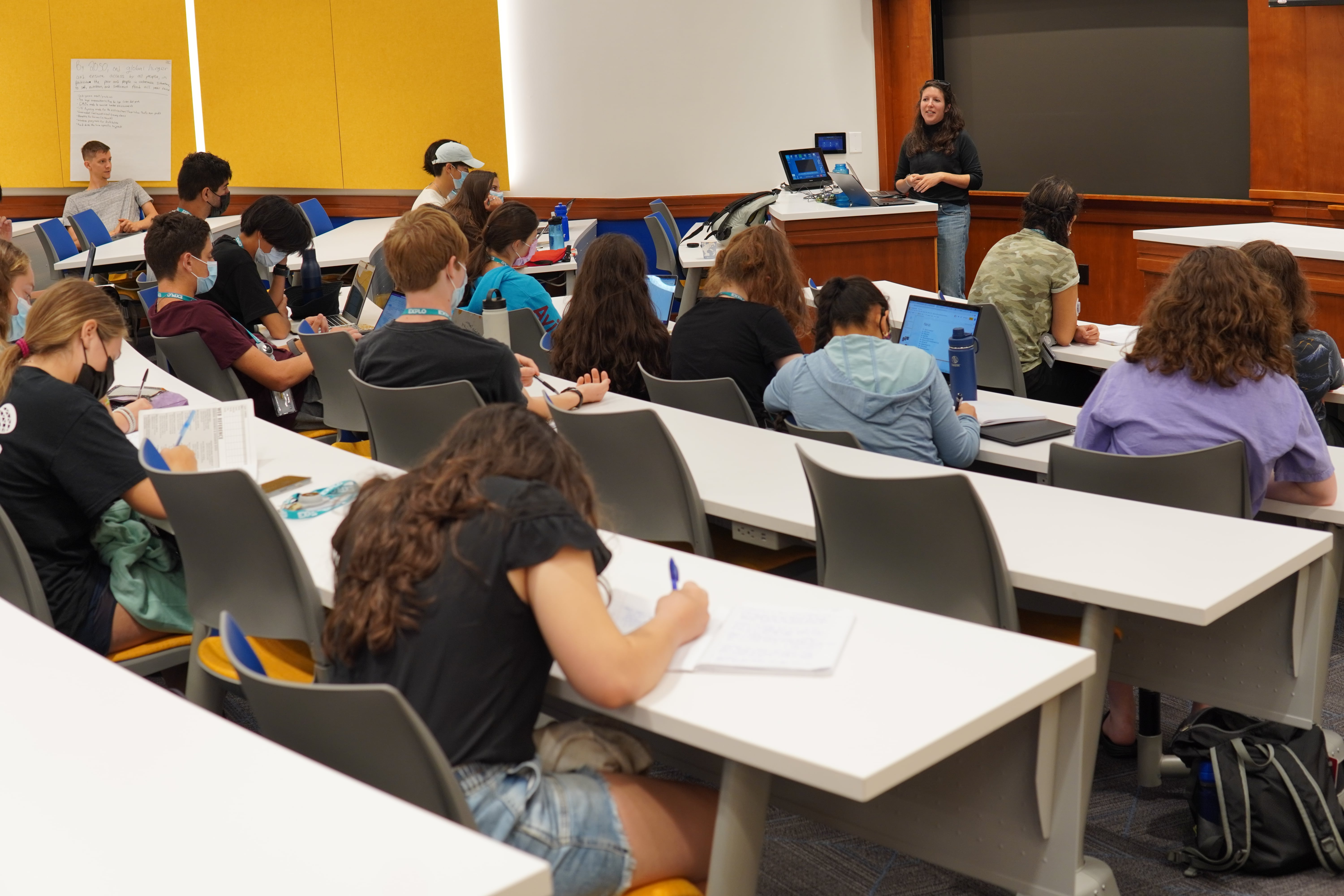 Students take their seats in a lecture hall for the guest speaker.
