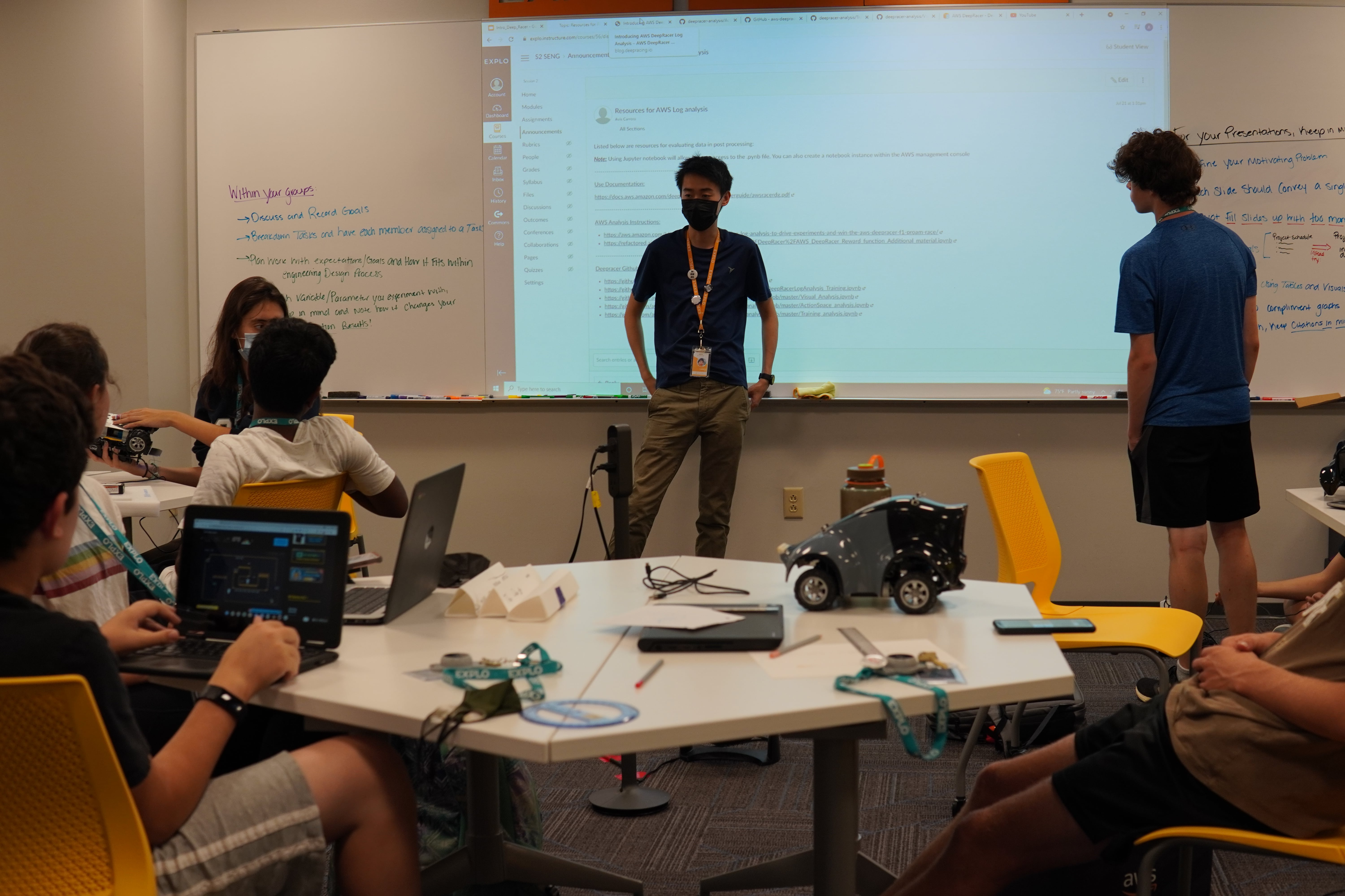 Teaching Fellow Lance speaks to students sitting at their tables to instruct them on the proper procedure for a step in their self driving car construction.