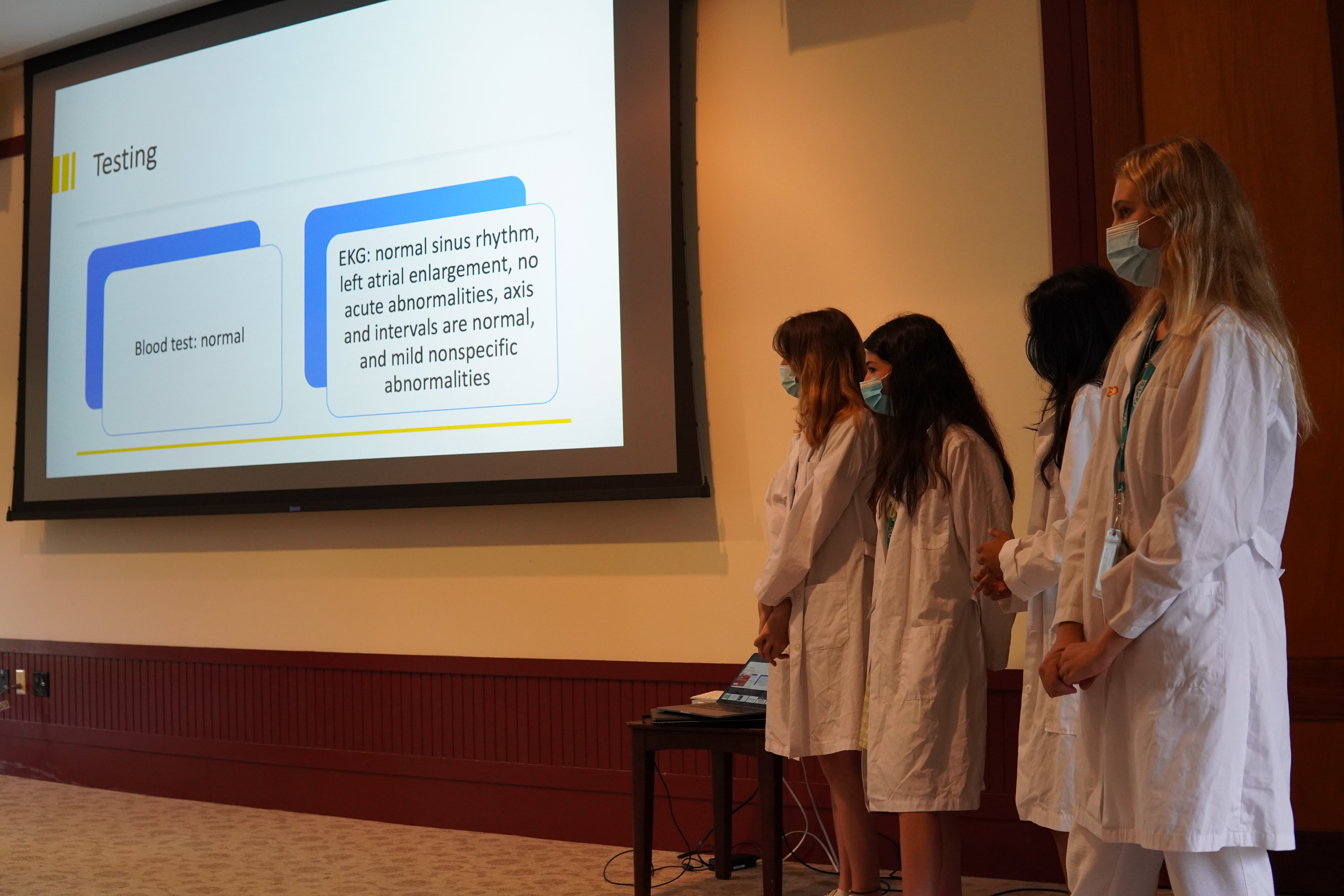 Students take their place at the front of the lecture hall and begin discussing the test they did on their hypothetical patient.