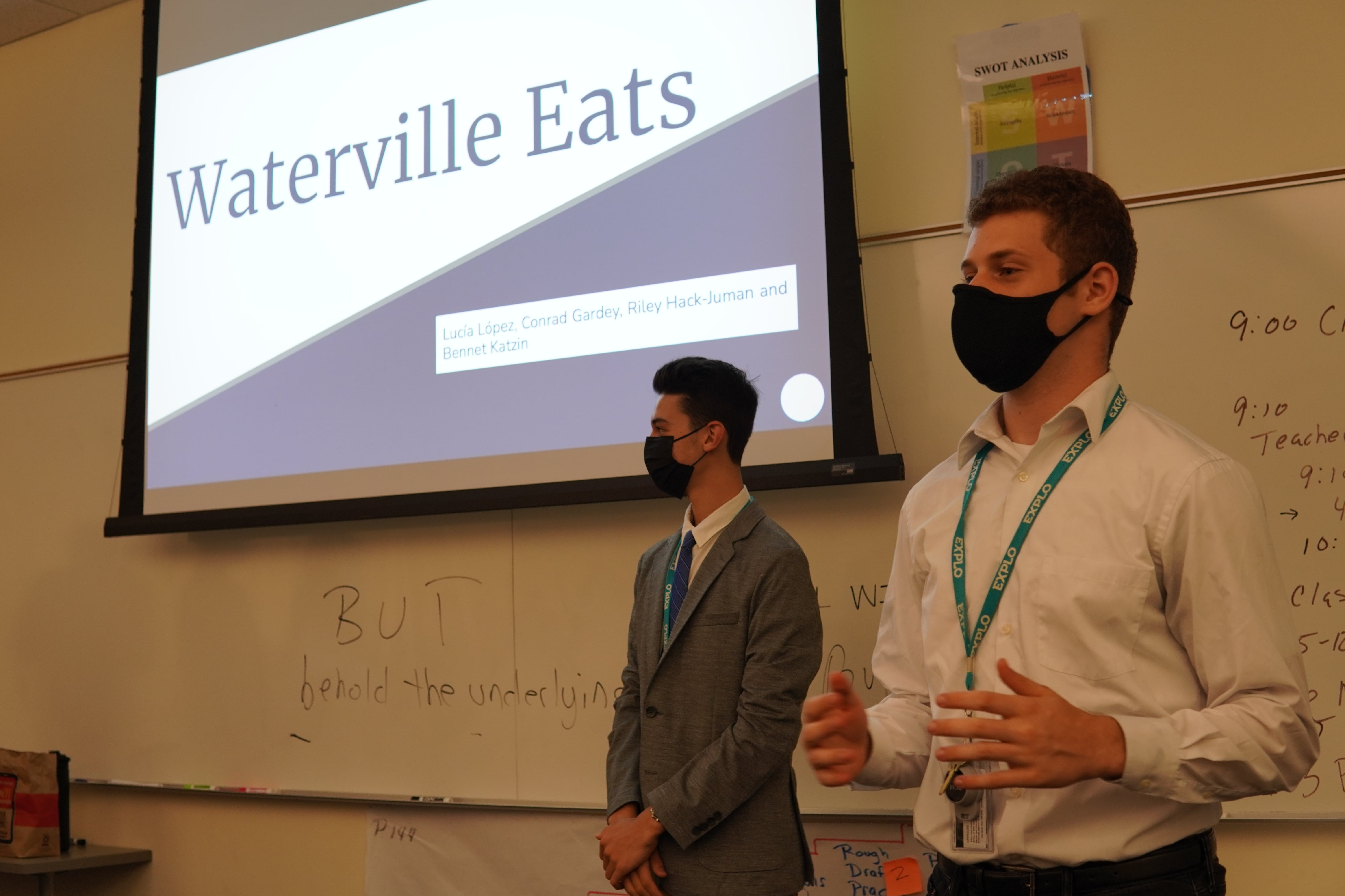 Students stand at the front of the room under a projector displaying the title slide of their business plan: Waterville Eats.