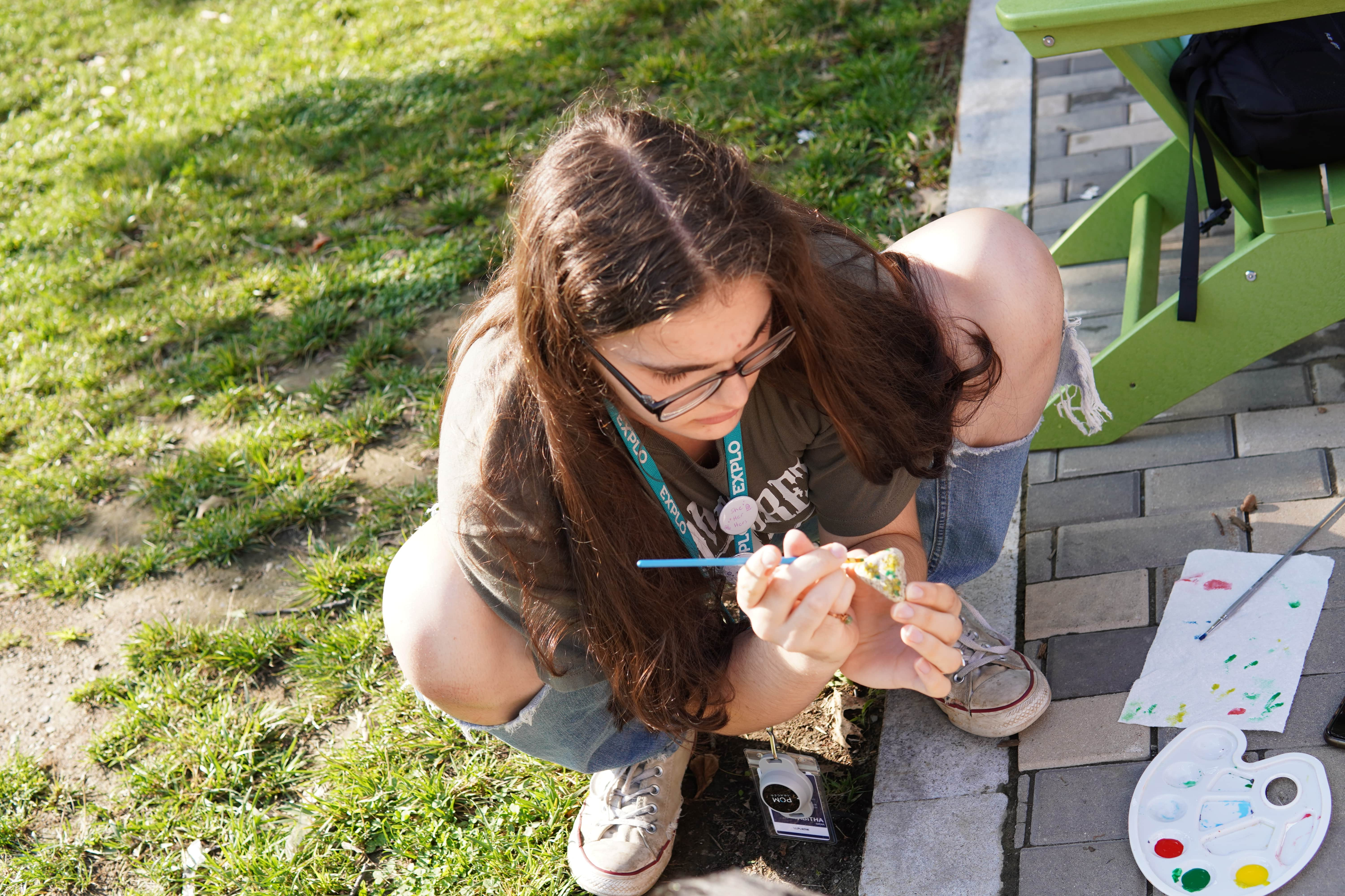 A student squats on the ground to paint their pet rock.