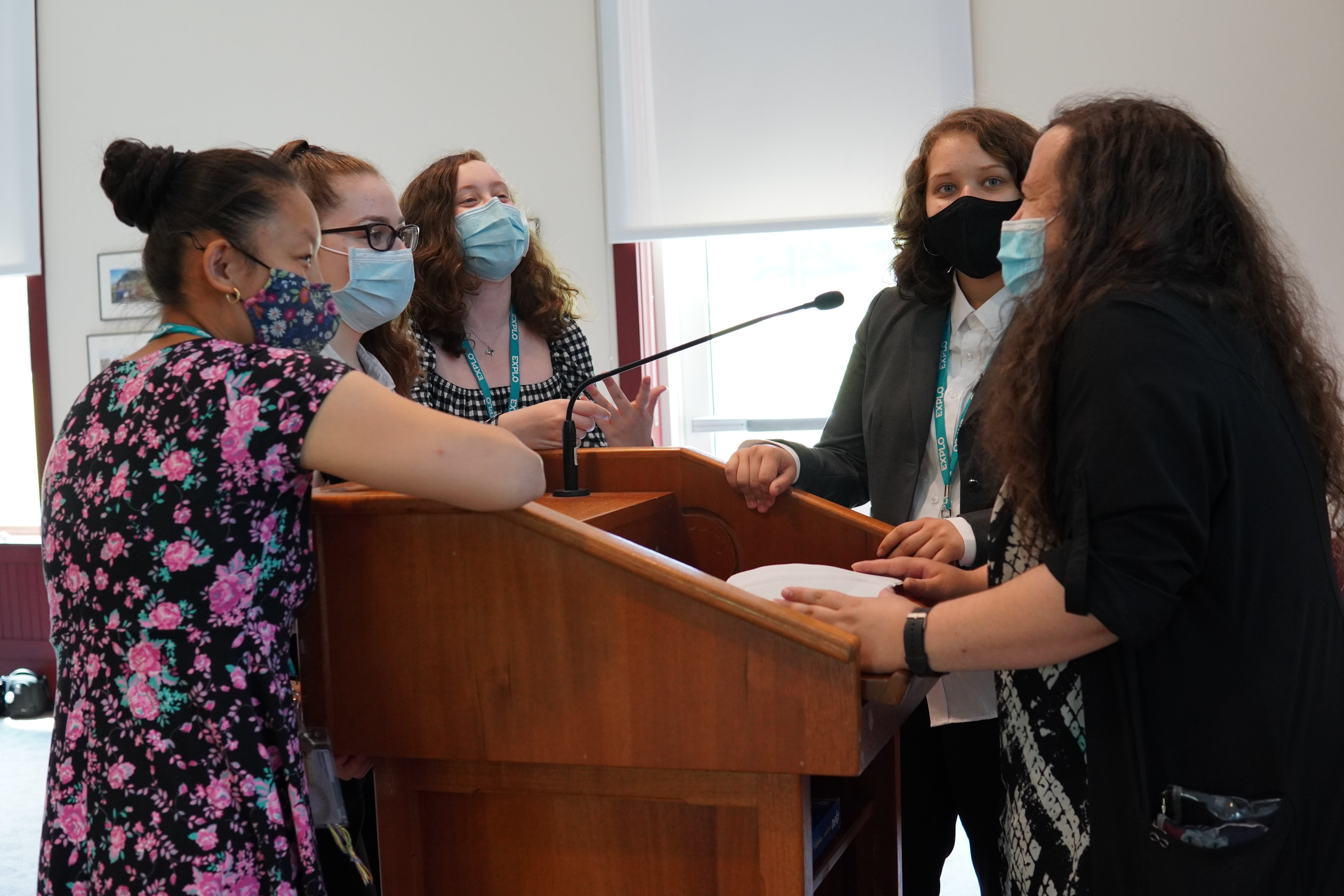 Teaching Fellow Adriana meets with students at the podium to test the mic and share a laugh.