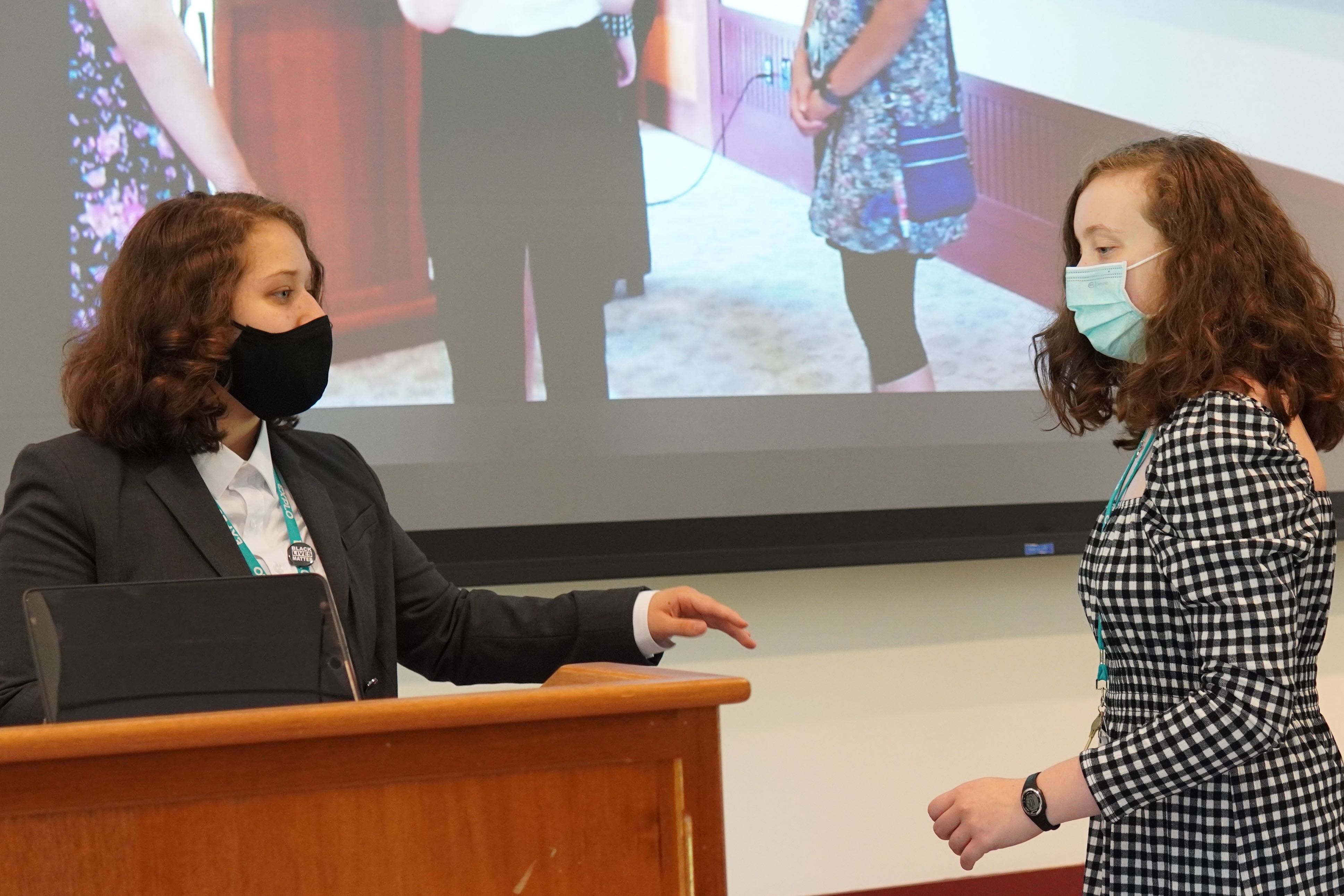 Two students practice their presentation before others arrive to see themselves projected on the screen.