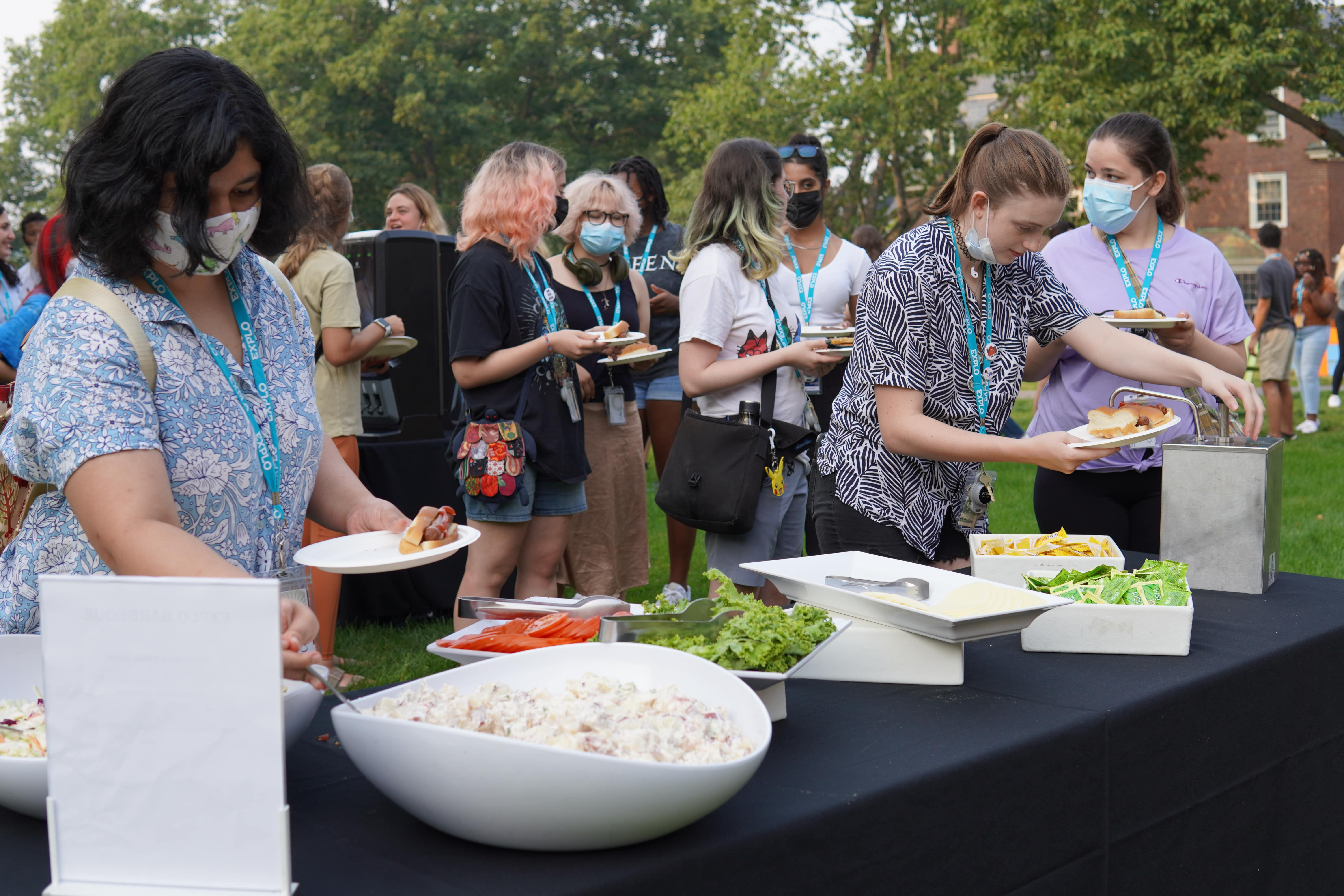 Students surround the side table where one grabs a spoonful of potato salad and another pumps ketchup onto their burger.