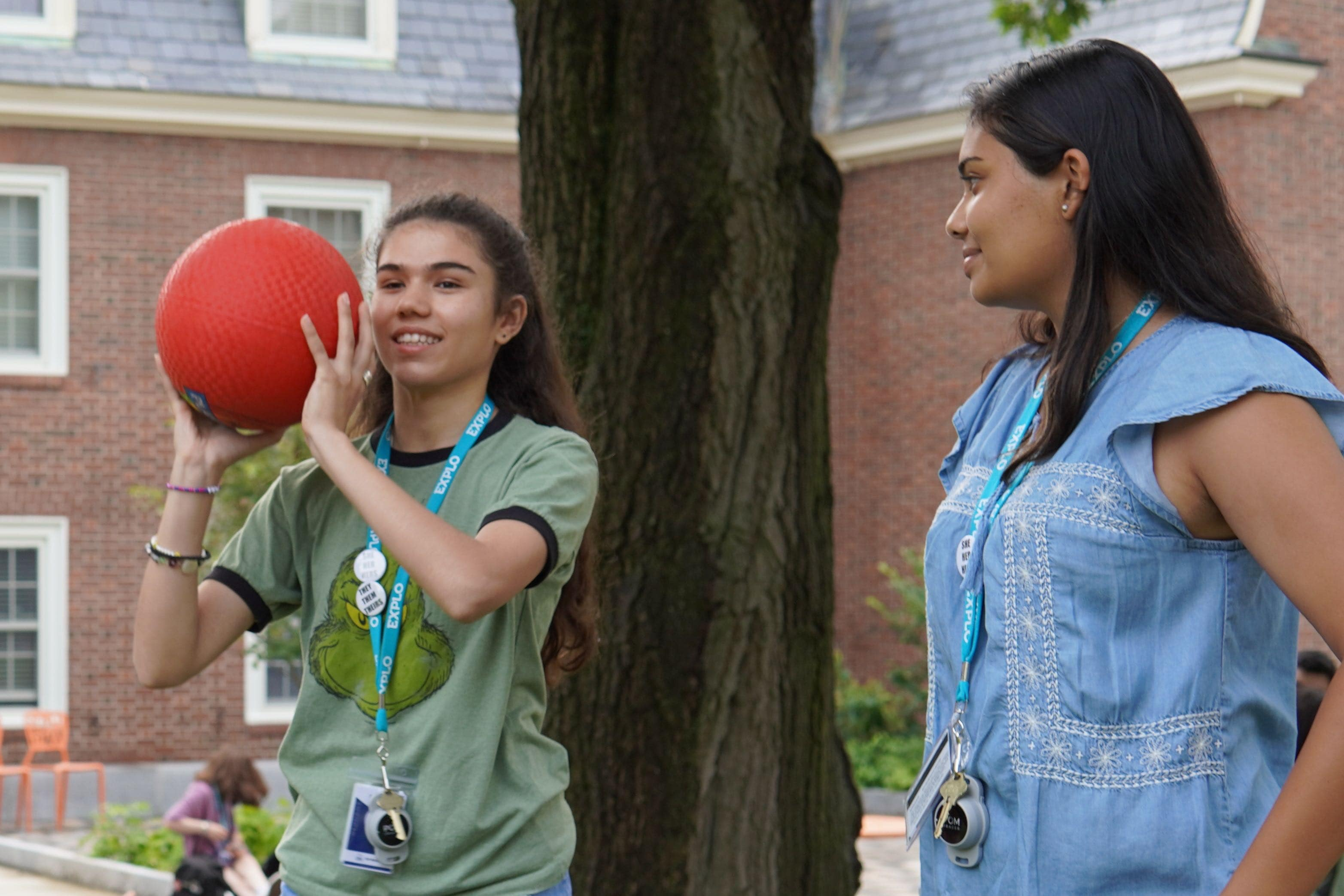 A student prepares to throw a red rubber ball as they stand in a circle next to their peers.