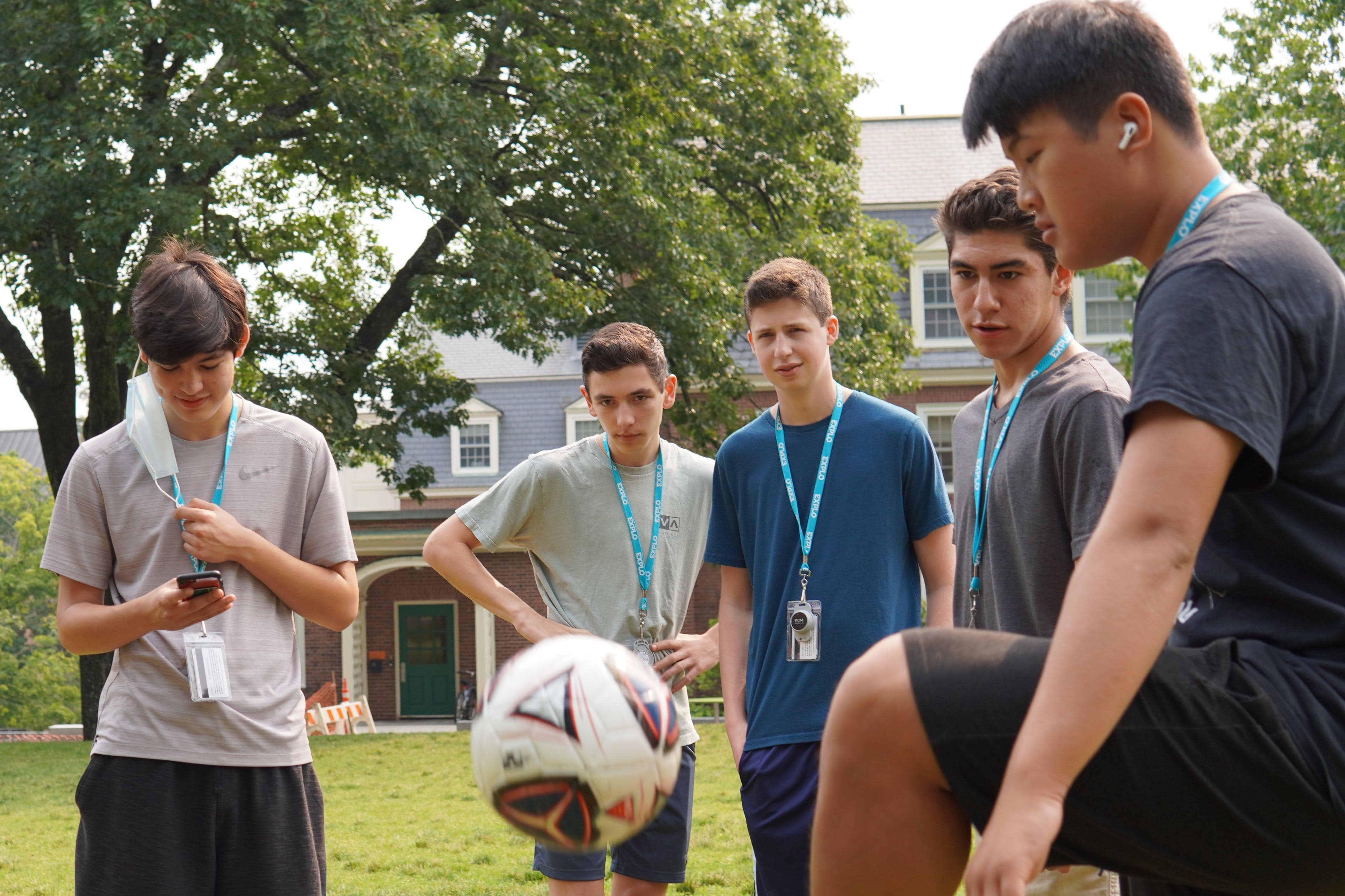 Students gather in a circle to kick a soccer ball between them as they wait for the community meeting to start on the quad.