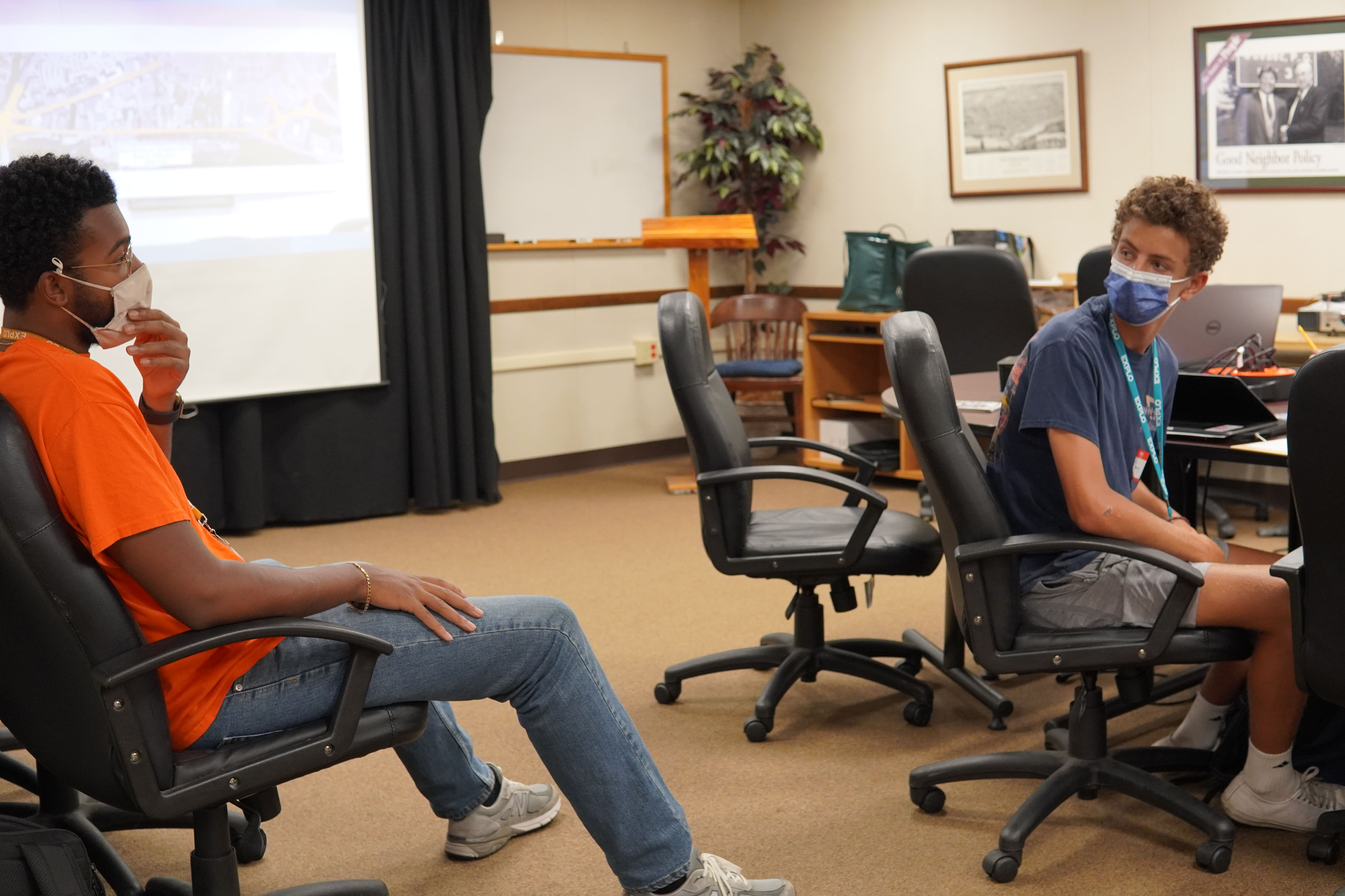 Teaching Fellow Justin and a student speak in a conference room before their meeting begins.