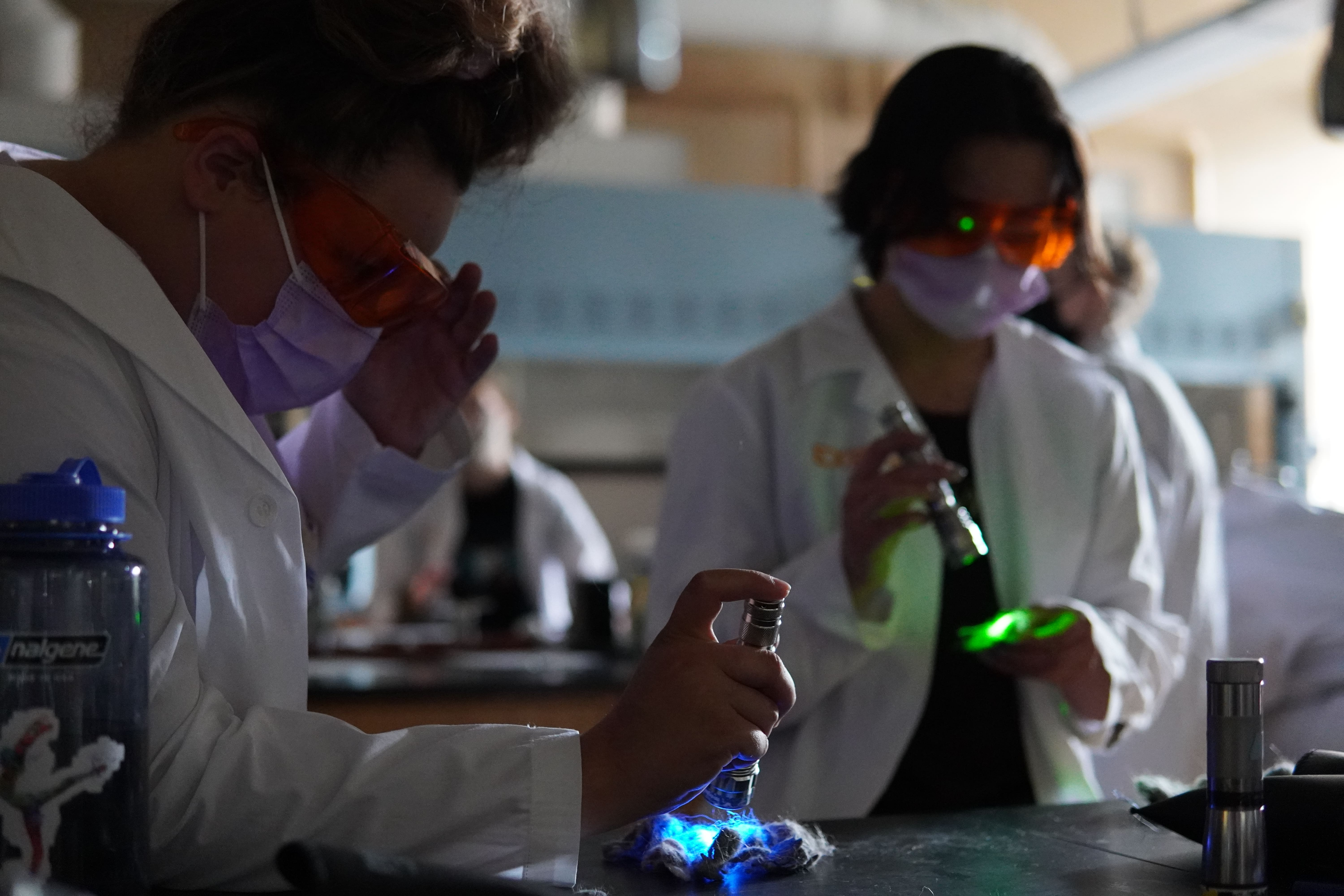 Two students stand in a dark room and use different colored flashlights to analyze materials in the hand.