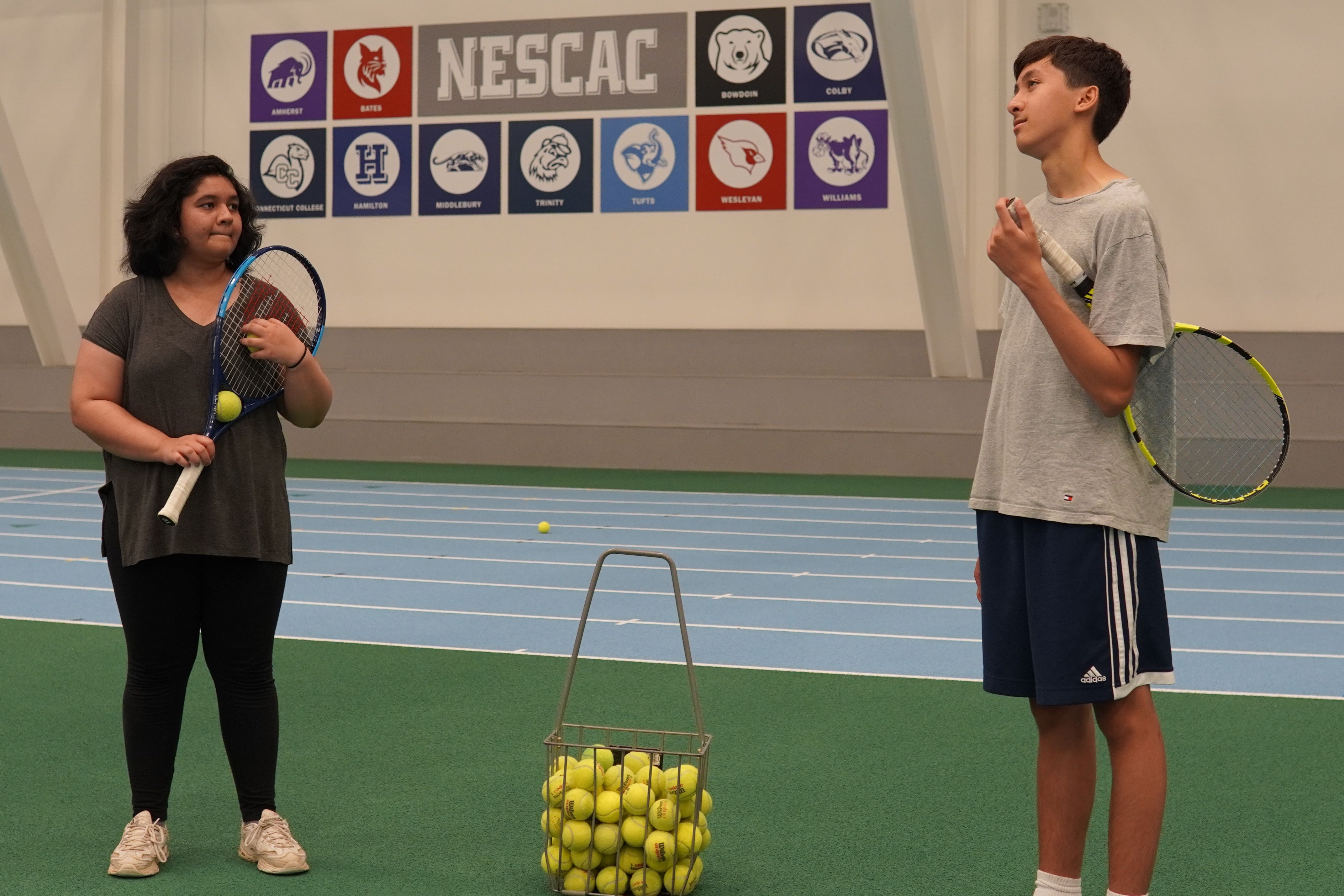 Students stand on the sides of a wire tennis ball bin and talk amongst themselves.