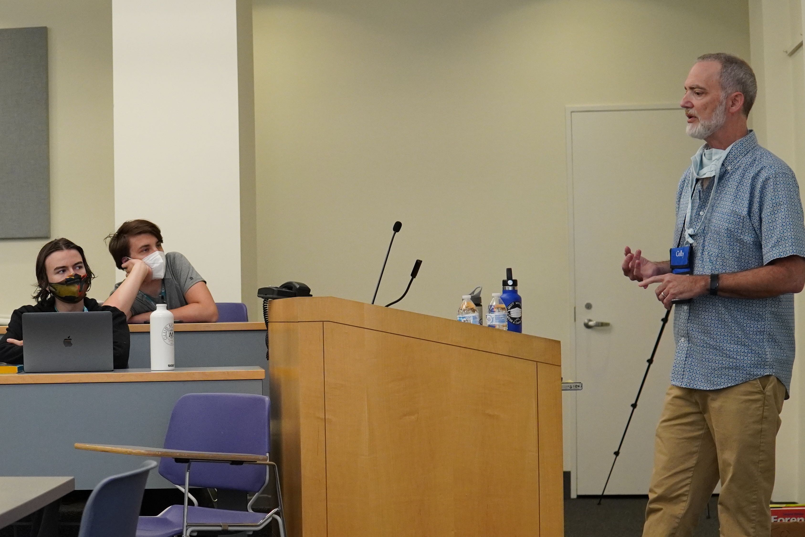 Greg Davis speaks in front of a podium while students listen in the audience.