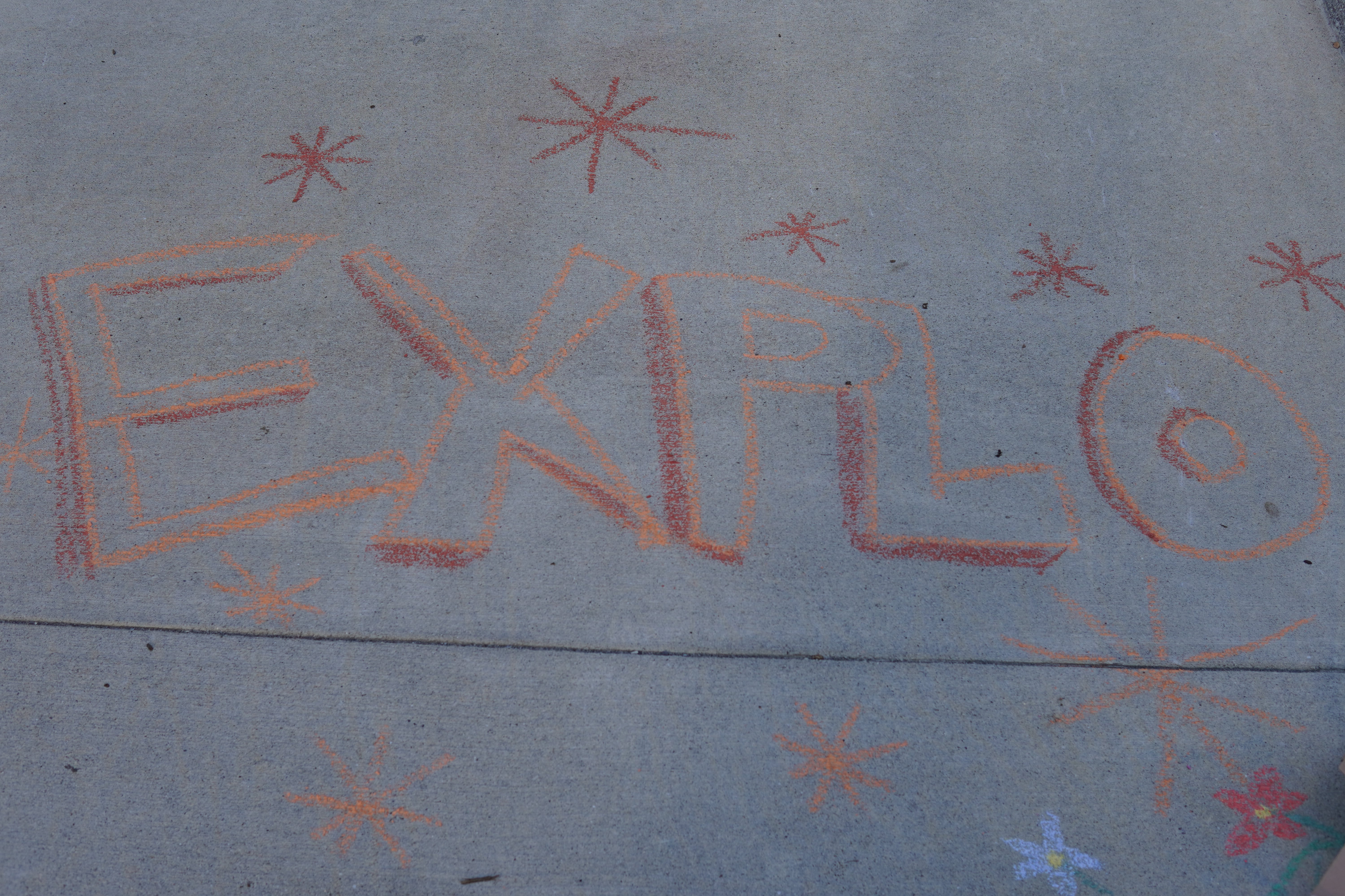 Red and orange chalk on the sidewalk spells out EXPLO