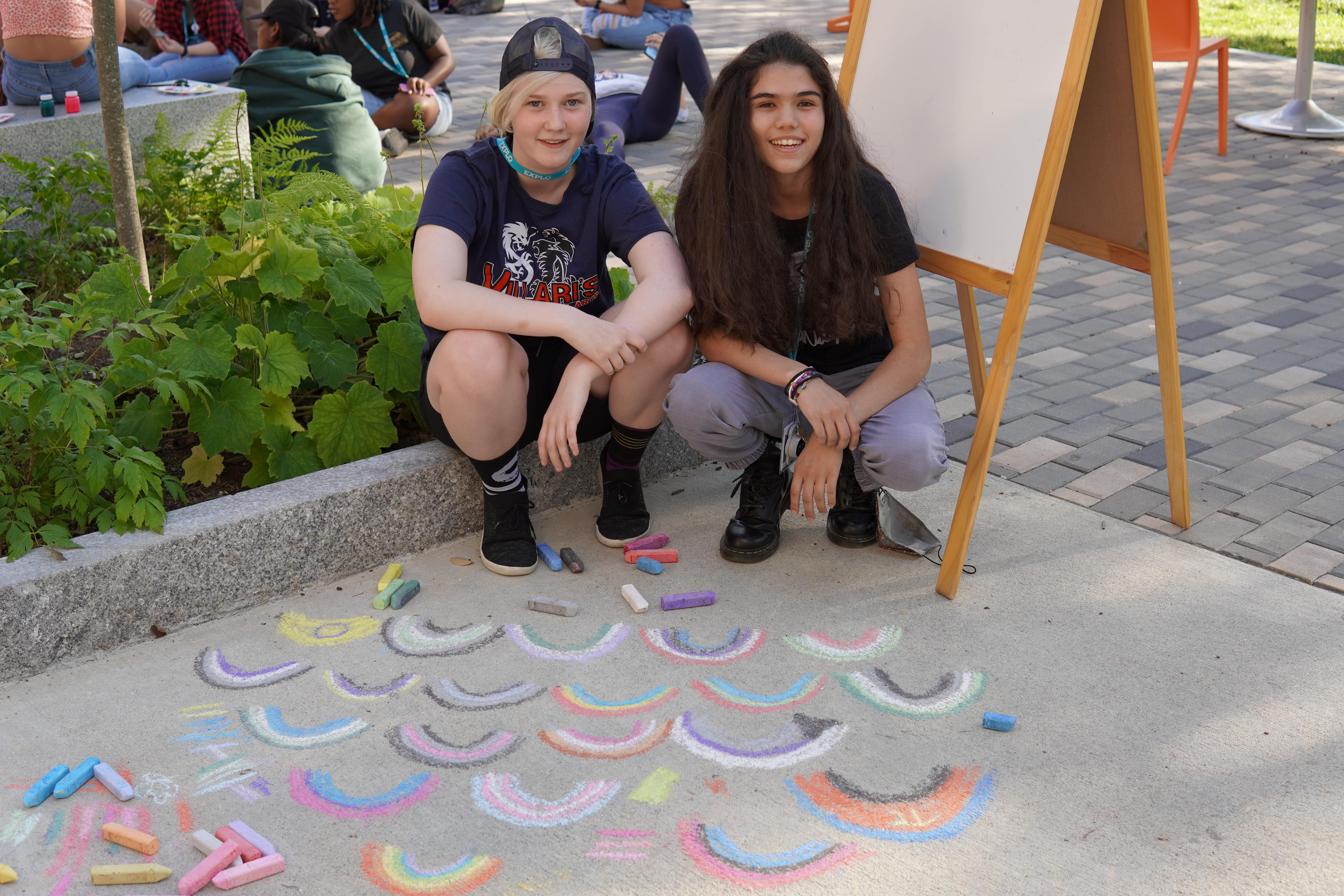 Two students sit next to the chalk Pride rainbows they drew on the sidewalk.