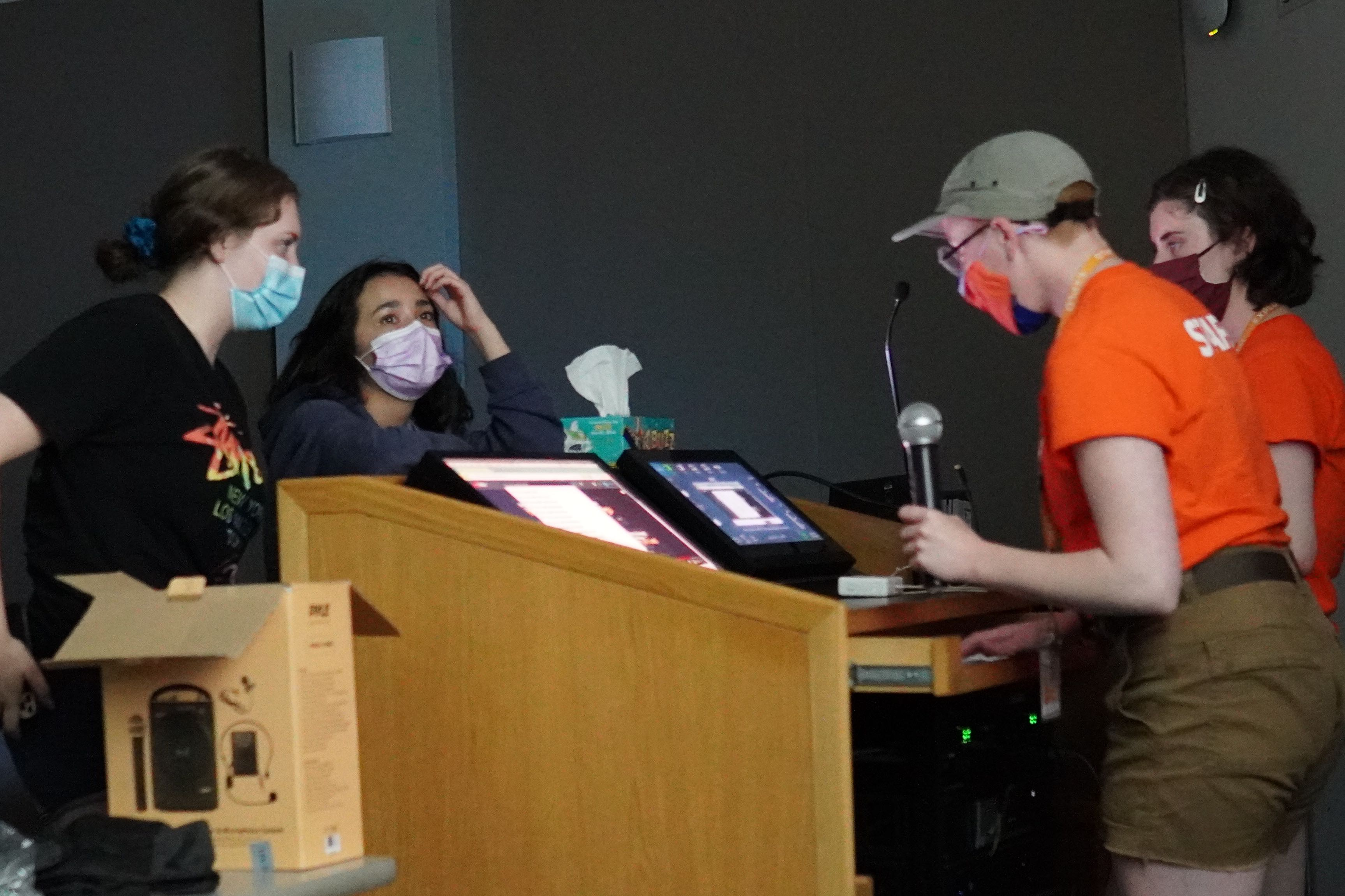 Students stand in front of a podium and announce their song to staff members pulling the lyrics up on the computer and projector for karaoke.
