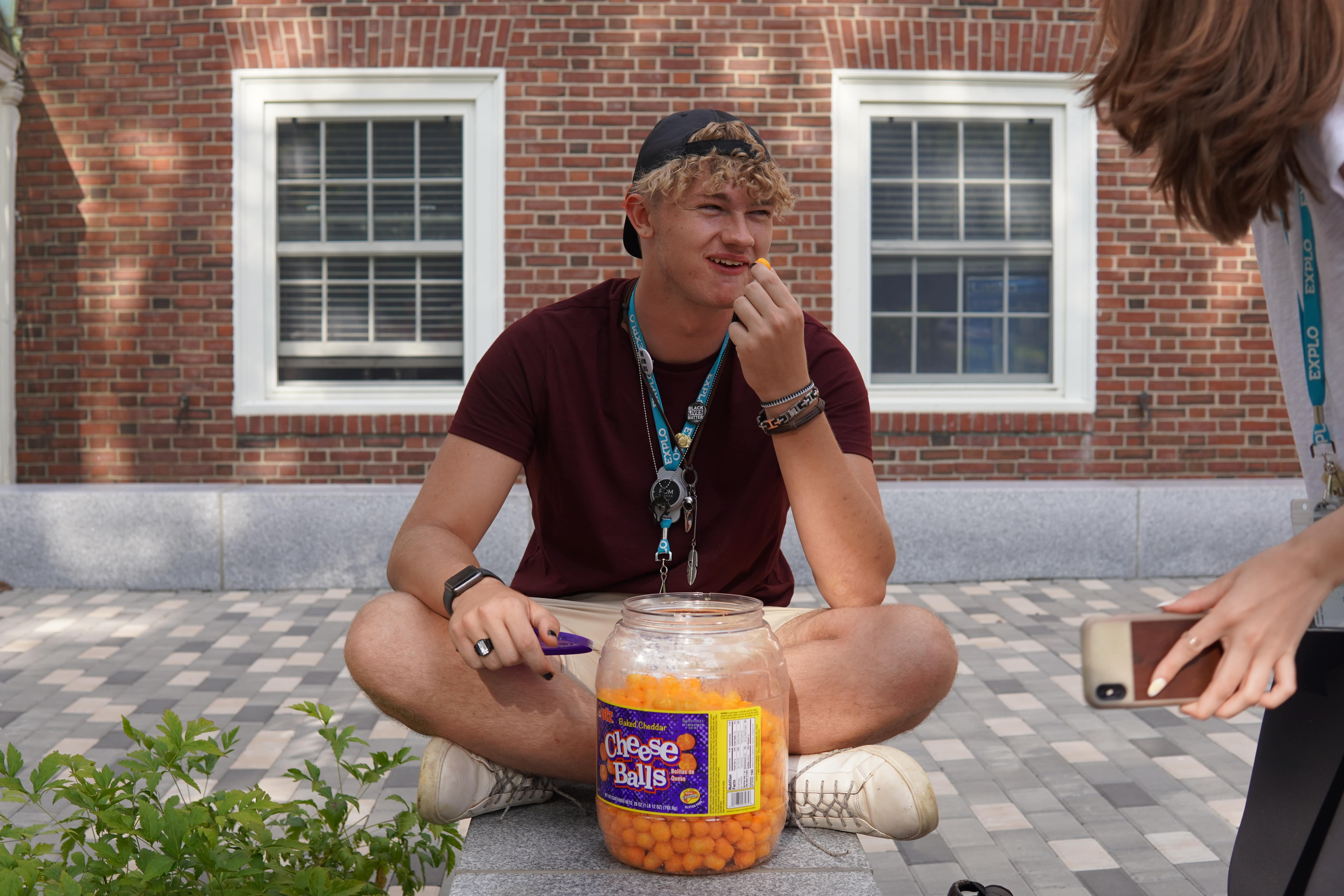 A student sits crosslegged with a large jar of cheese balls in front of them as they snack on them.