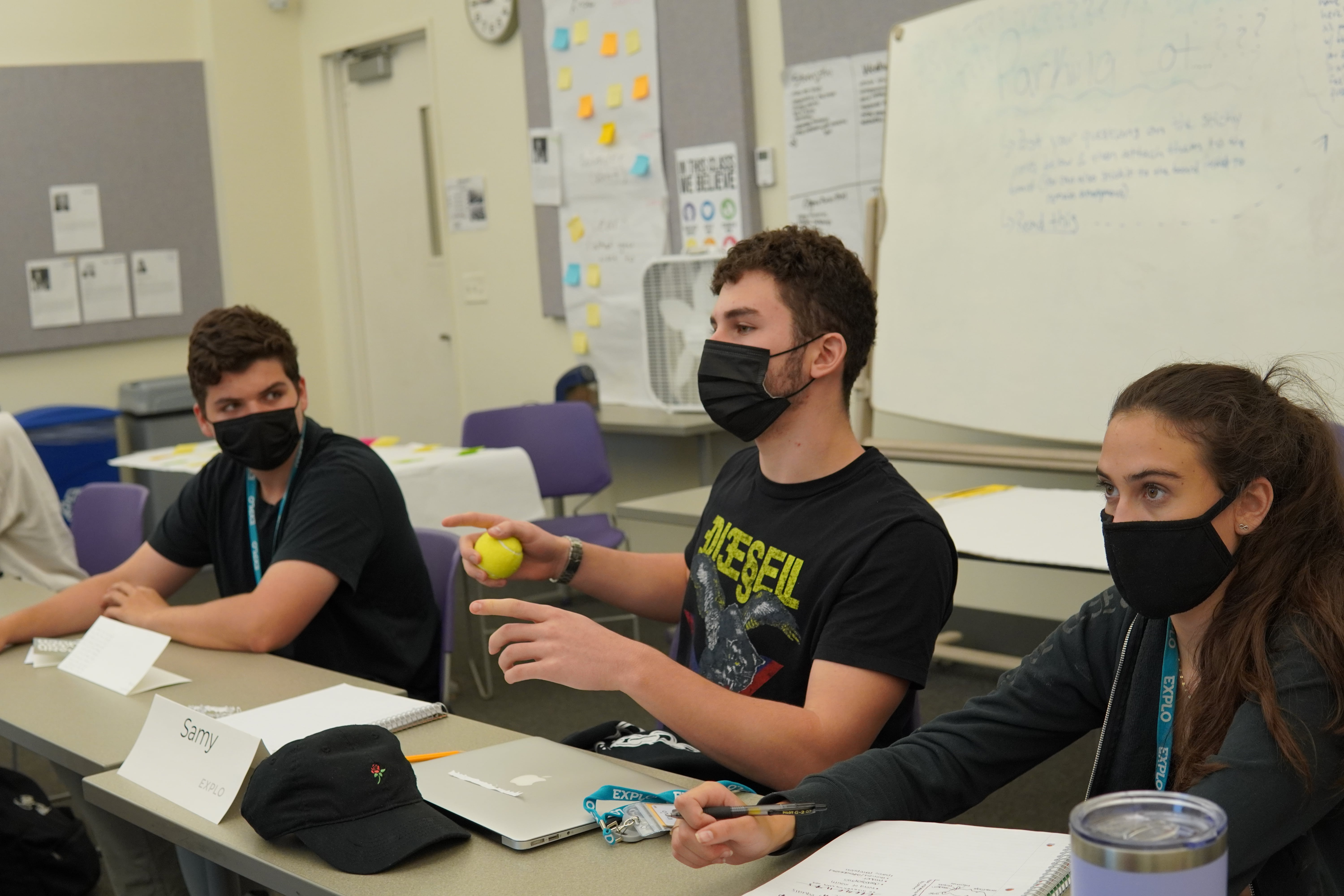 A student holds a tennis ball to denote them as the speaker as they outline their ideas for reaching a younger audience.