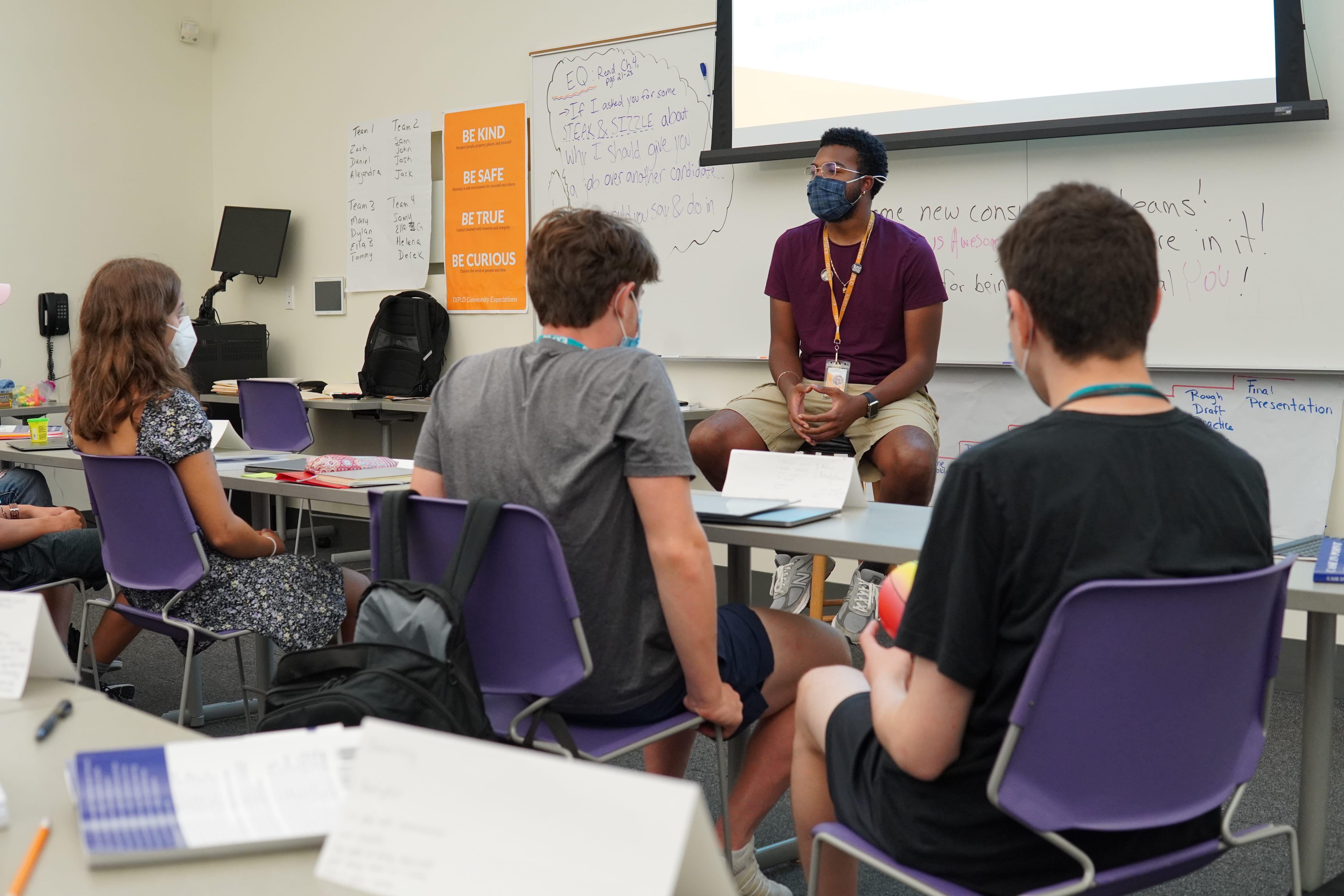 Teaching Fellow Justin sits at the front of the room and listens to students' strategies for reaching different target demographics.