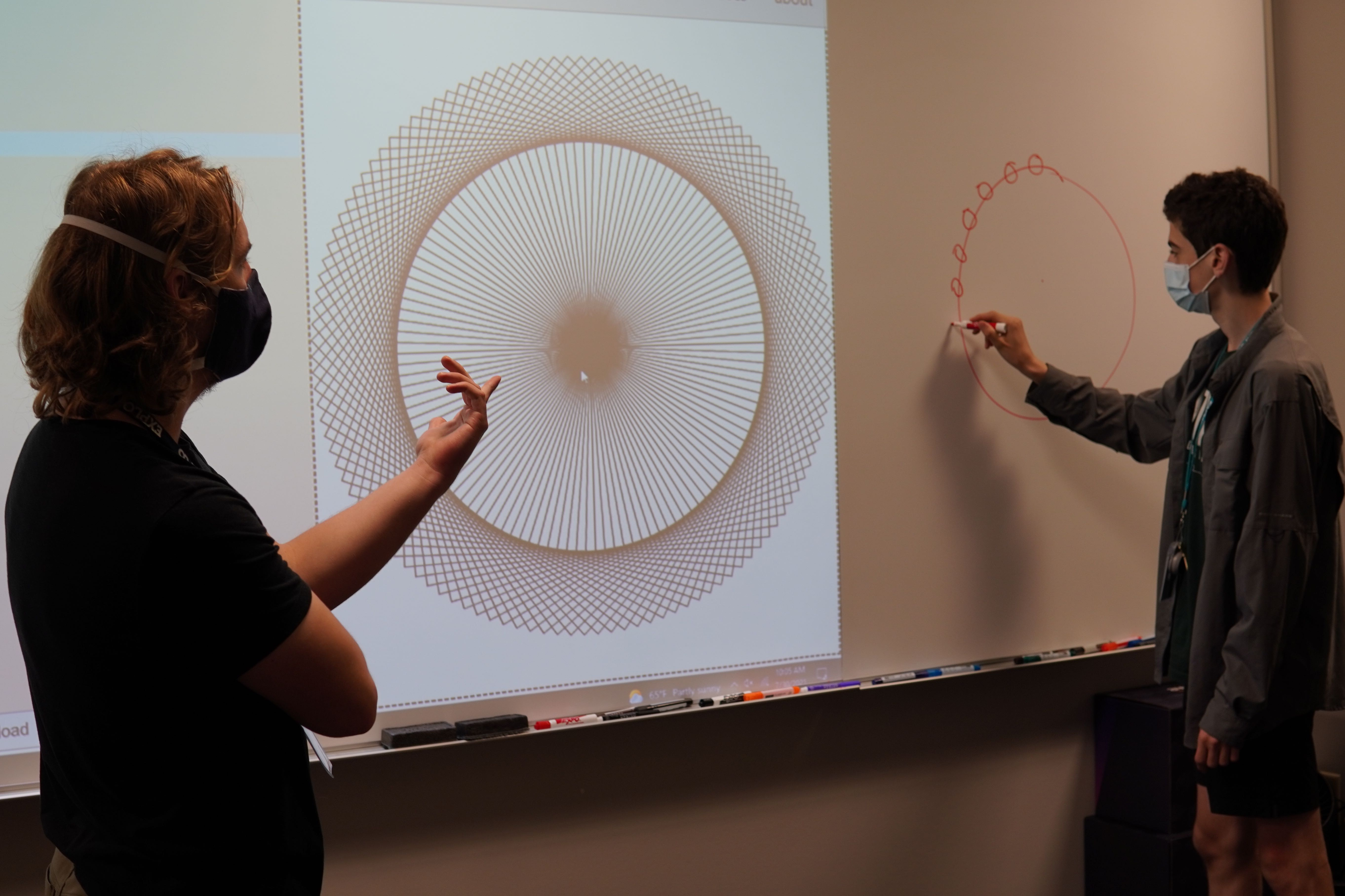 Leo McElroy speaks with a student after they brought their coded shapes on the projector. The student is drawing the shape they are attempting to make on the white board.
