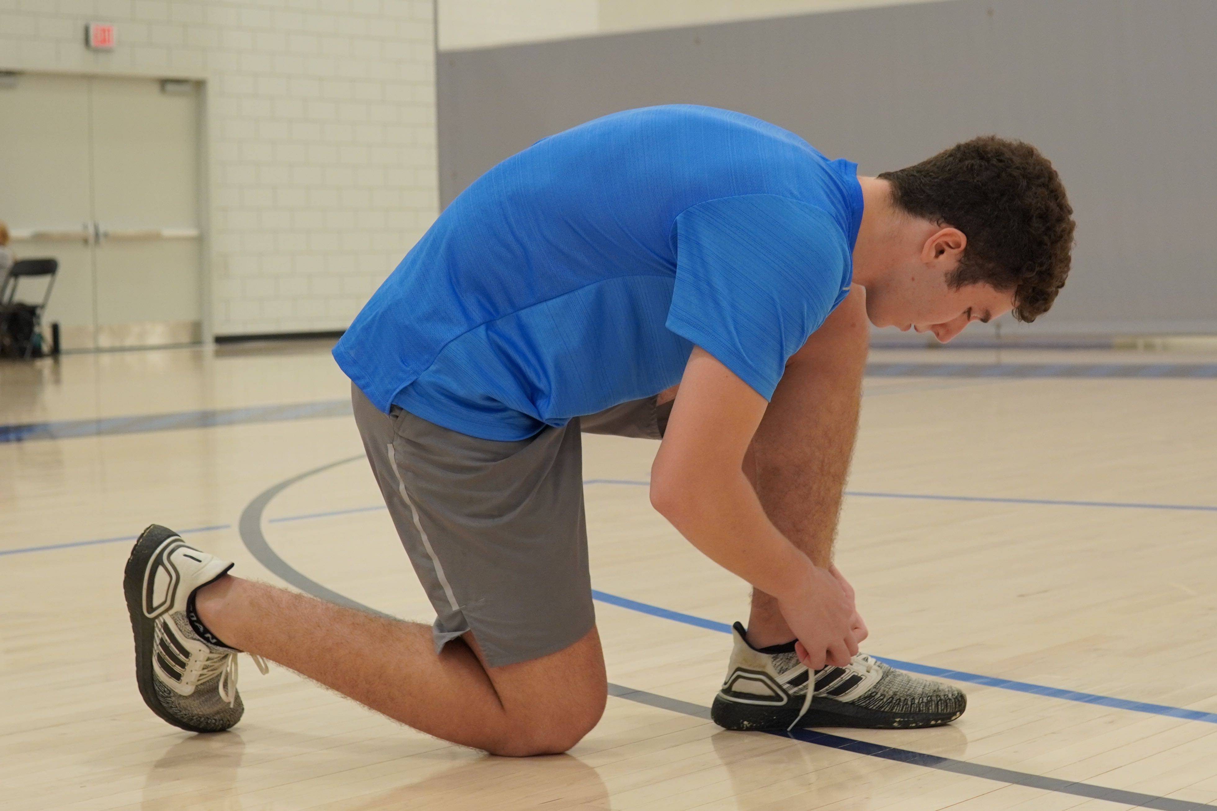 A student kneels to tie their shoes on the court.