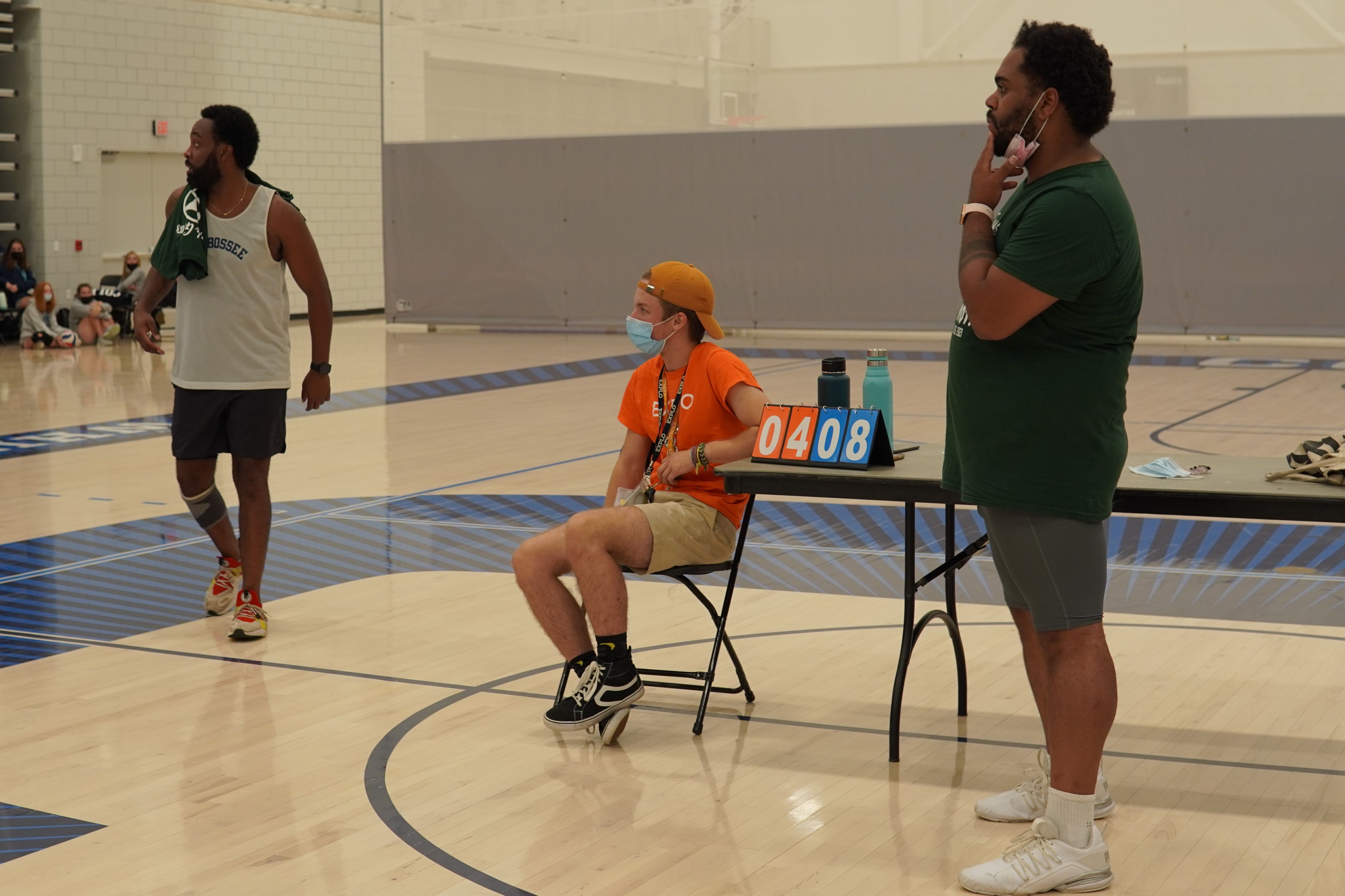 Three staff members stand off the court and coach their teams during a game.