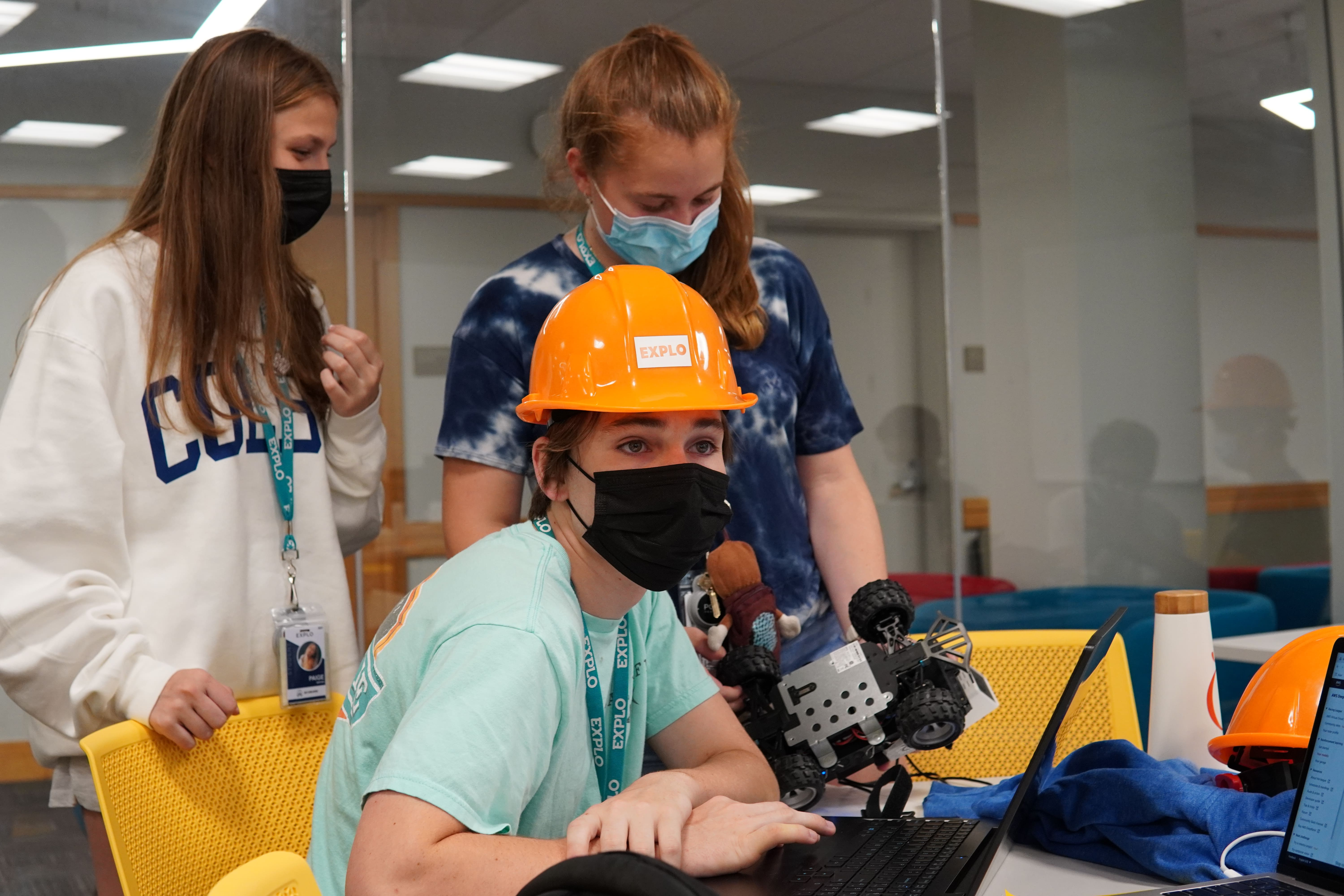 A student in an EXPLO hardhat works on their computer as two students behind them examine their car.