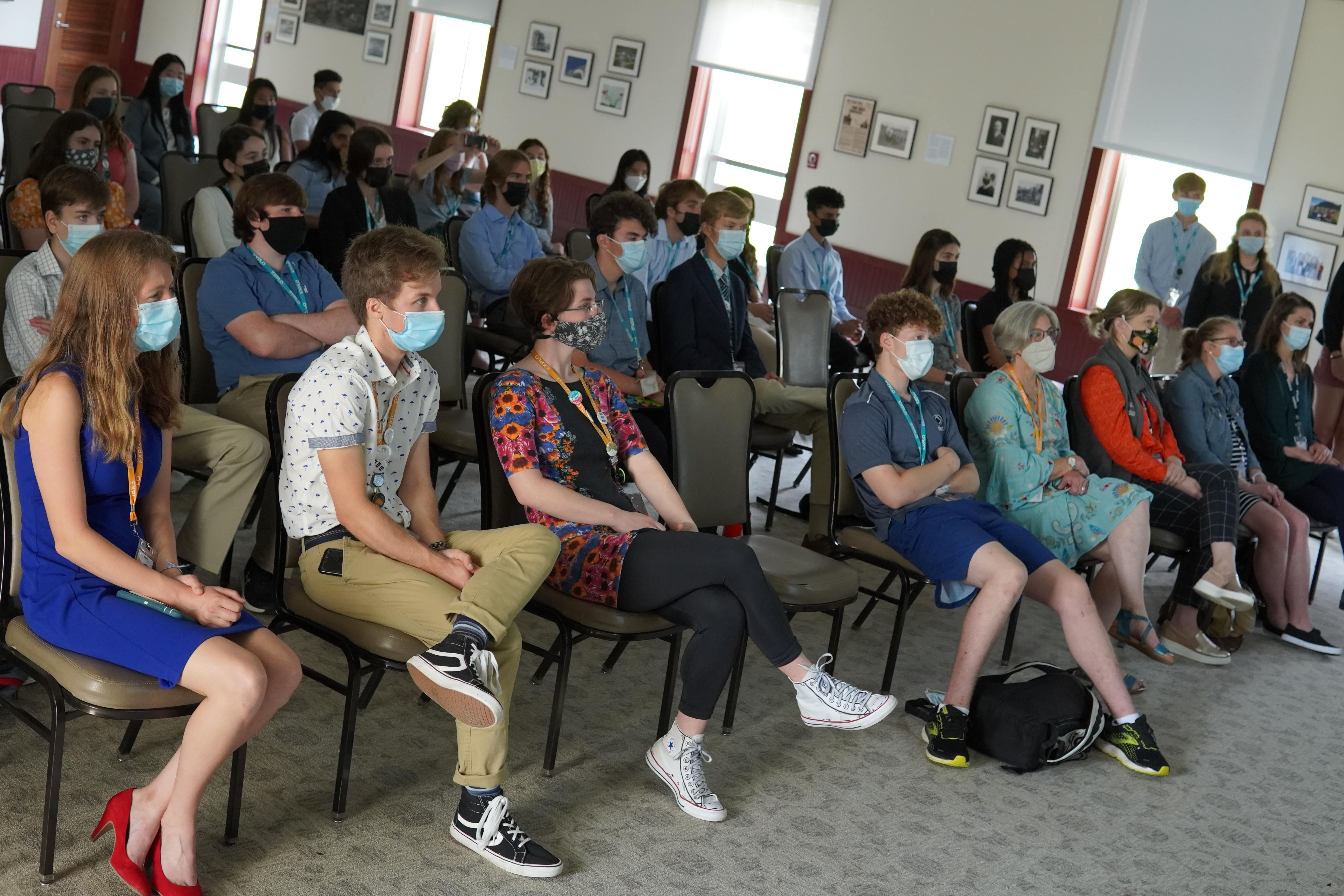 Students and staff sit in the audience and listen to presentations.