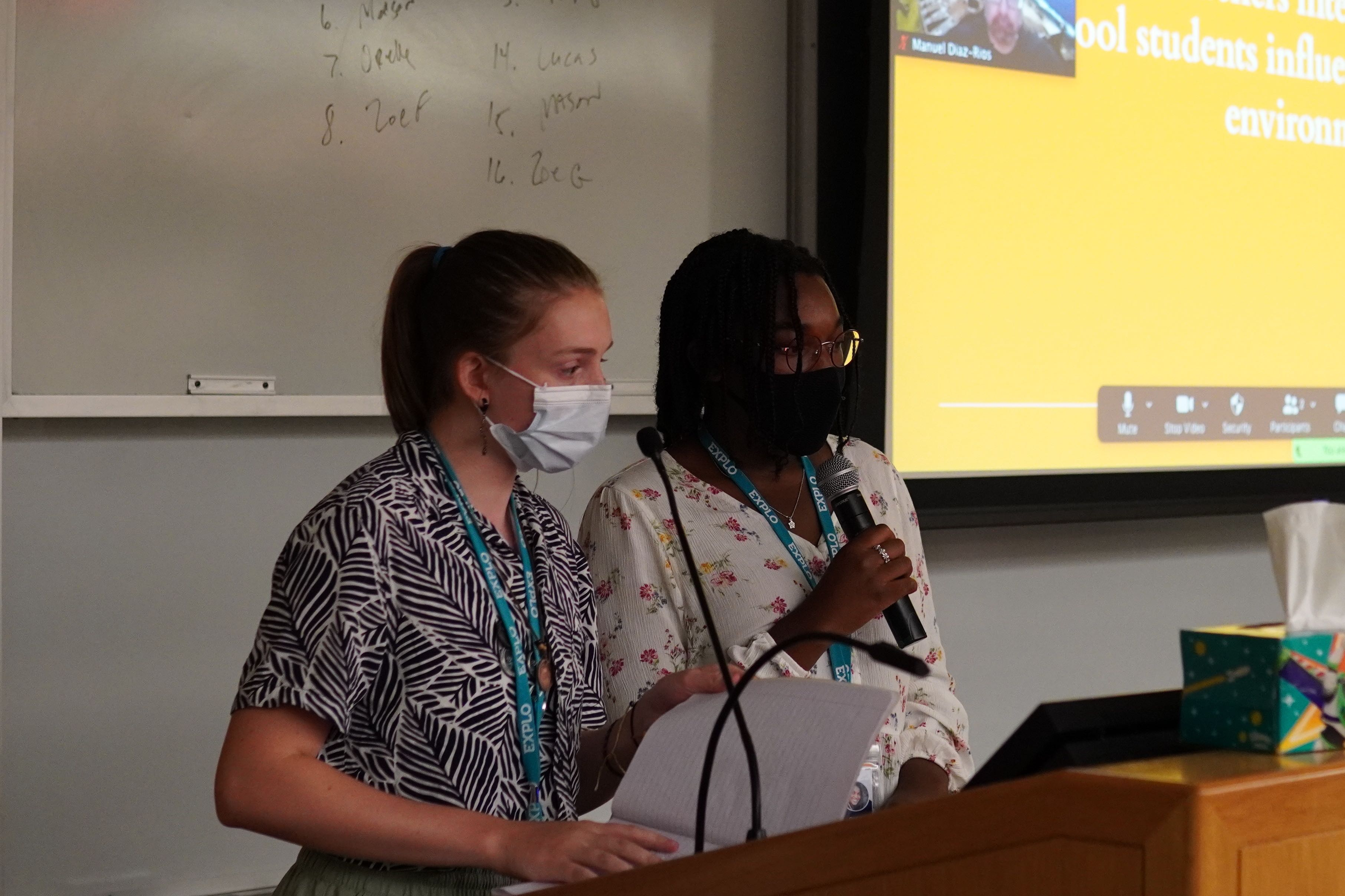 Two students stand at a podium and discuss their research.