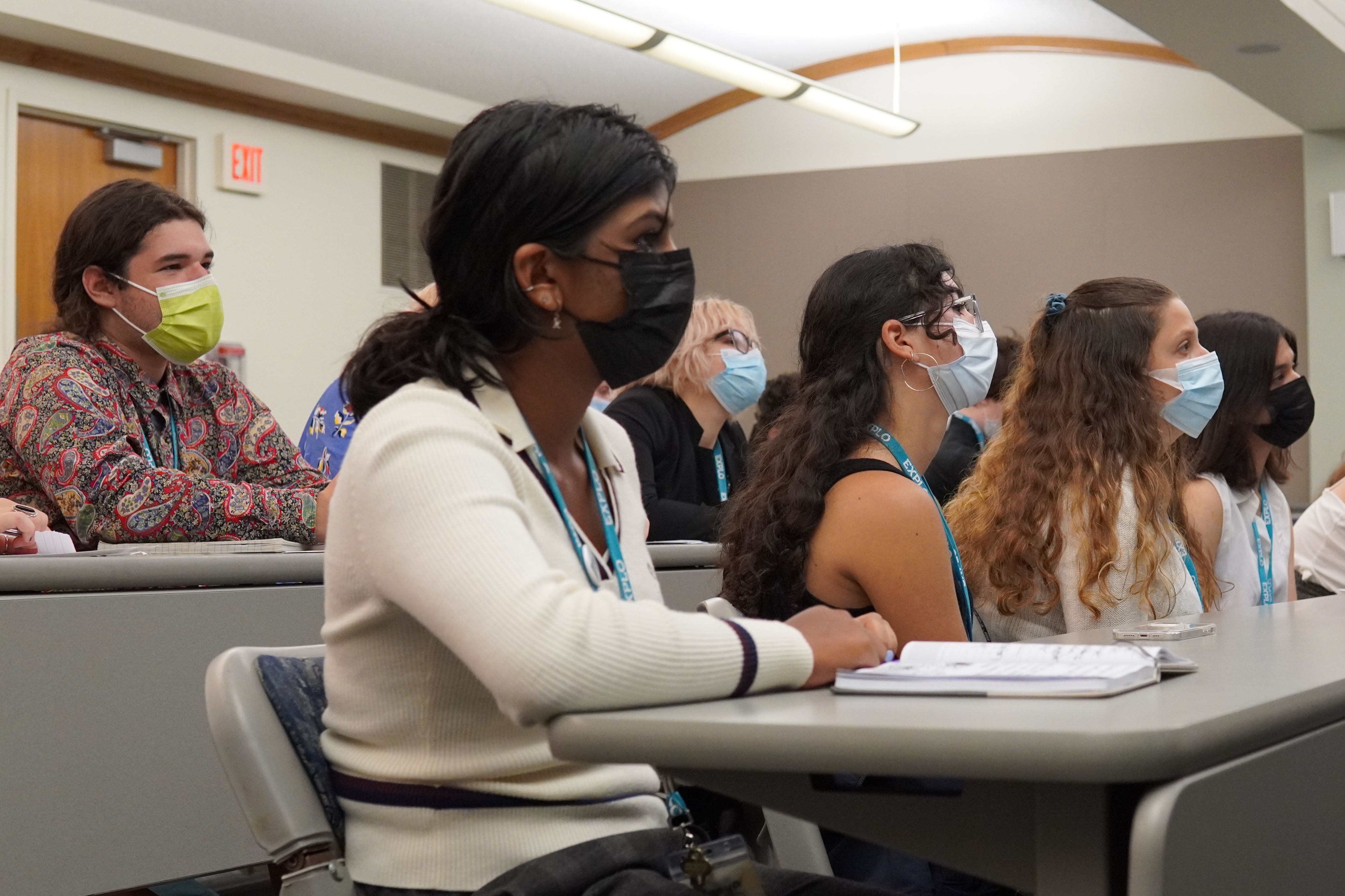 Students in the audience listen to their peers present their final research proposals.