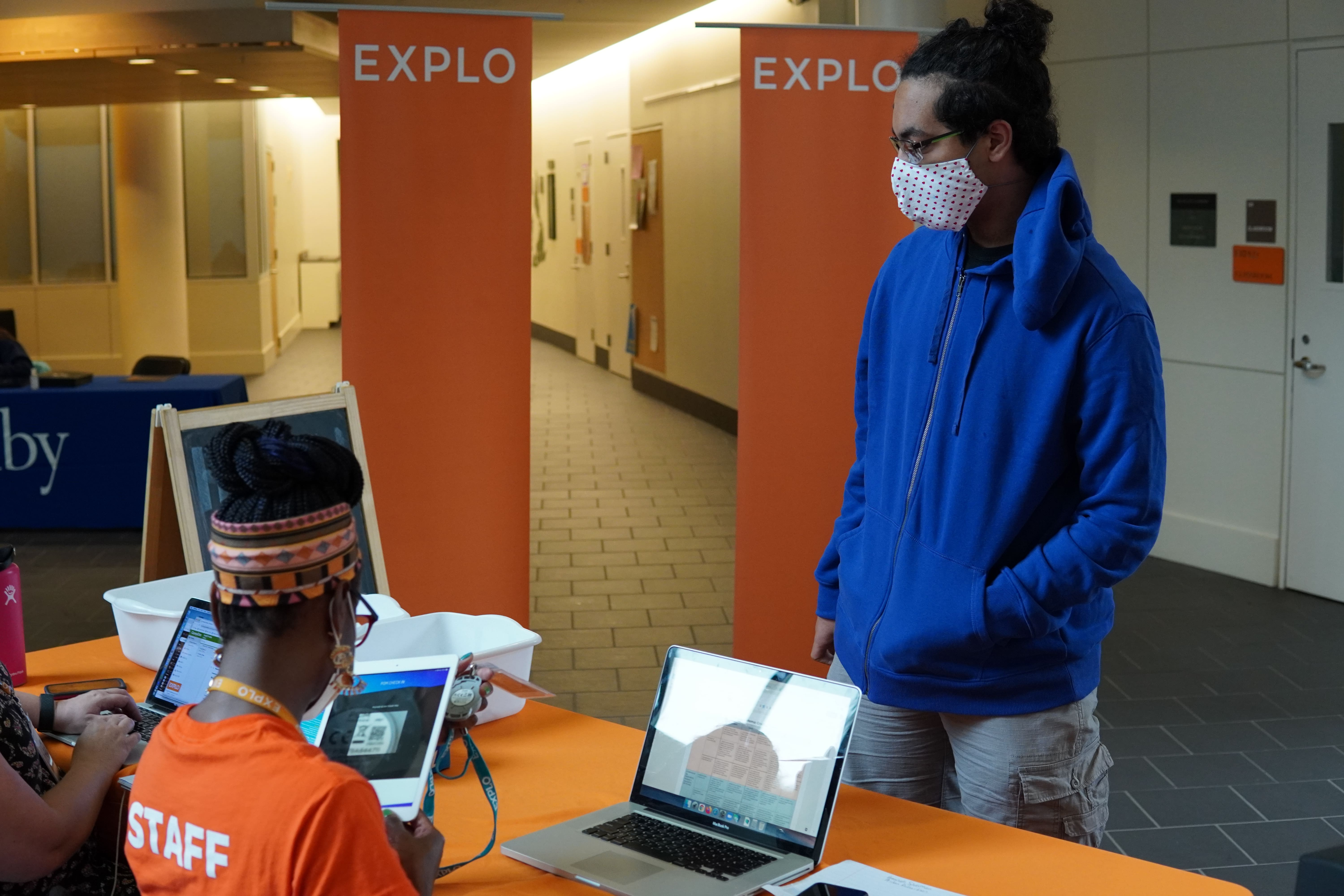 A student stands in front of the registration desk as they complete the final steps before they can go to their rooms and join the other students.
