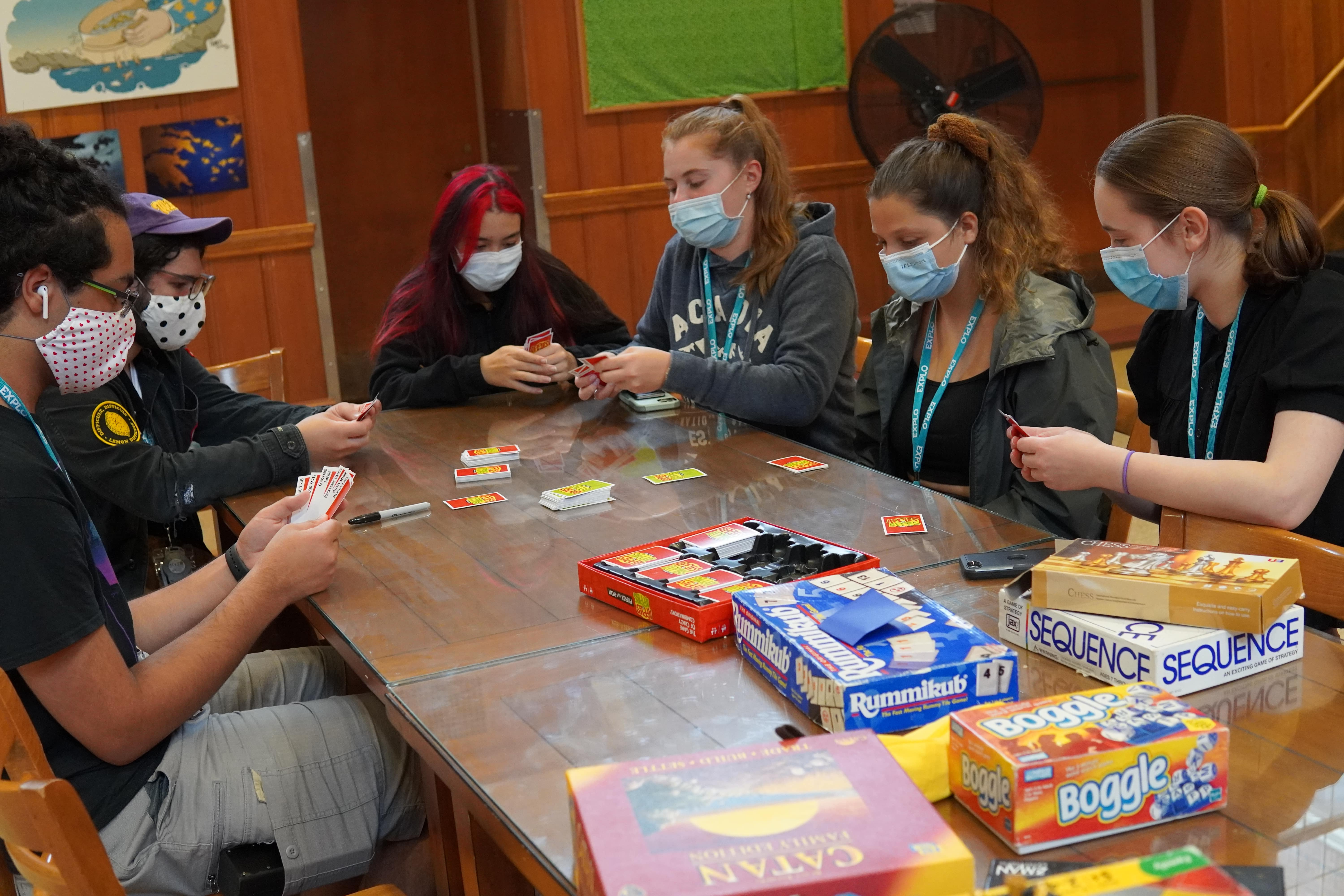 Students gather around a table and begin looking at their Apples to Apples cards.
